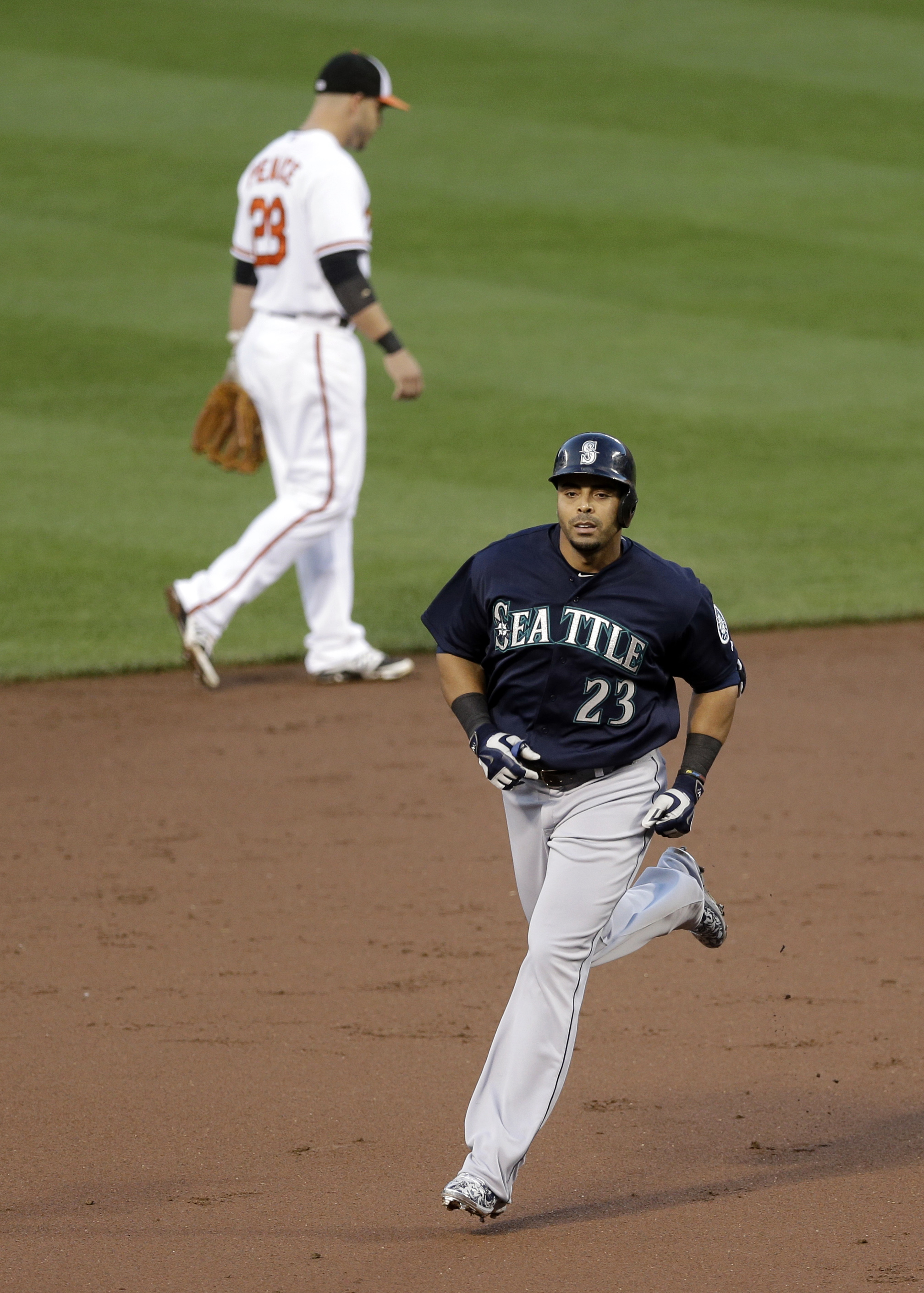 Seattle Mariners' Nelson Cruz rounds the bases past Baltimore Orioles second baseman Steve Pearce after hitting a three-run home run in the third inning of a baseball game, Tuesday, May 19, 2015, in Baltimore. (AP Photo/Patrick Semansky)