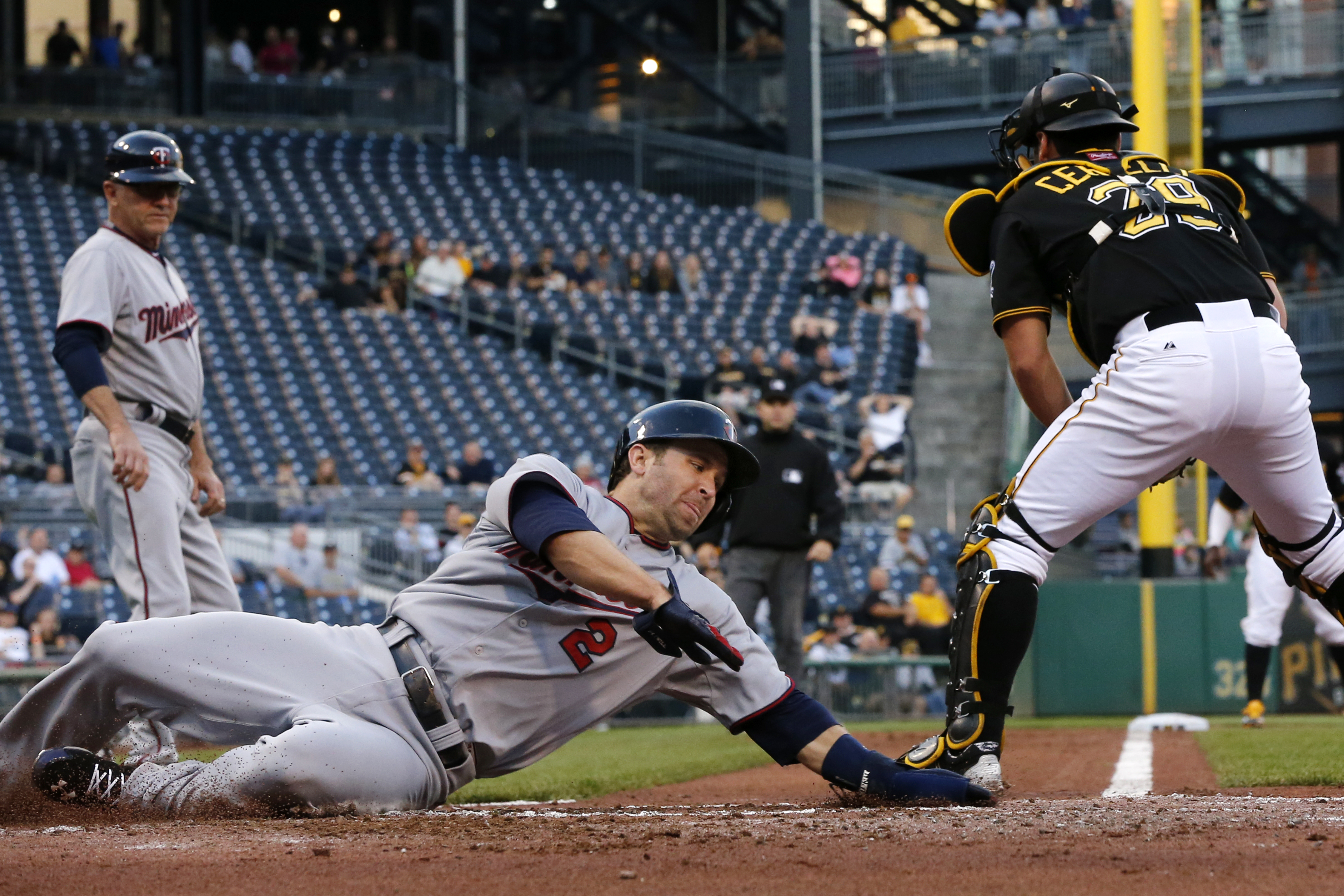 Minnesota Twins' Brian Dozier (2) slides around Pittsburgh Pirates catcher Francisco Cervelli (29) to score on a bases-loaded double by Joe Mauer off Pirates starting pitcher Francisco Liriano during the second inning of a baseball game in Pittsburgh on T
