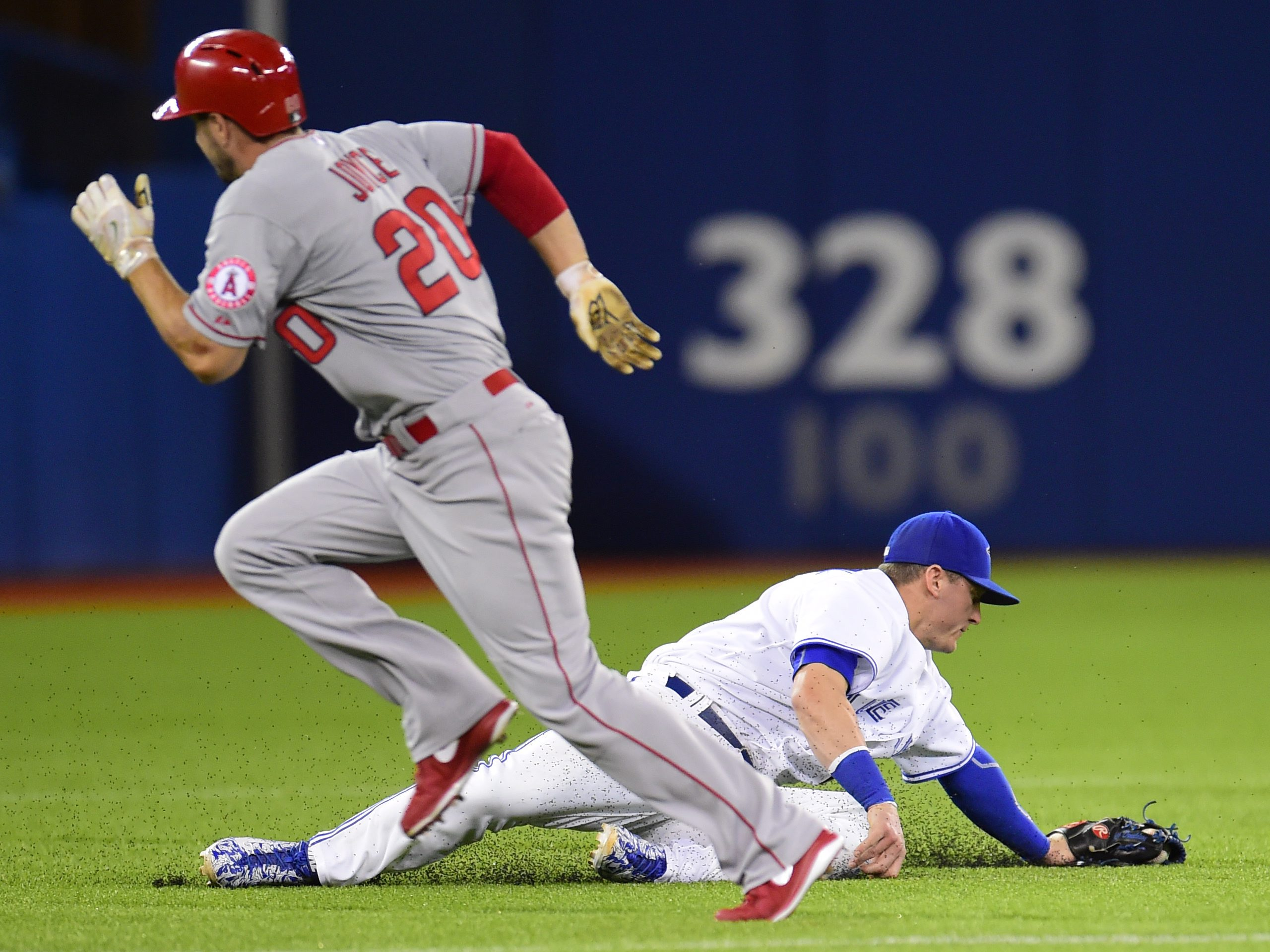 Toronto Blue Jays' Josh Donaldson stops a grounder  as Los Angeles  Angels' Matt Joyce (20) heads to third base during seventh inning American League baseball action in Toronto, Tuesday, May 19, 2015.  Donaldson  made the throw to force out Angels' Chris