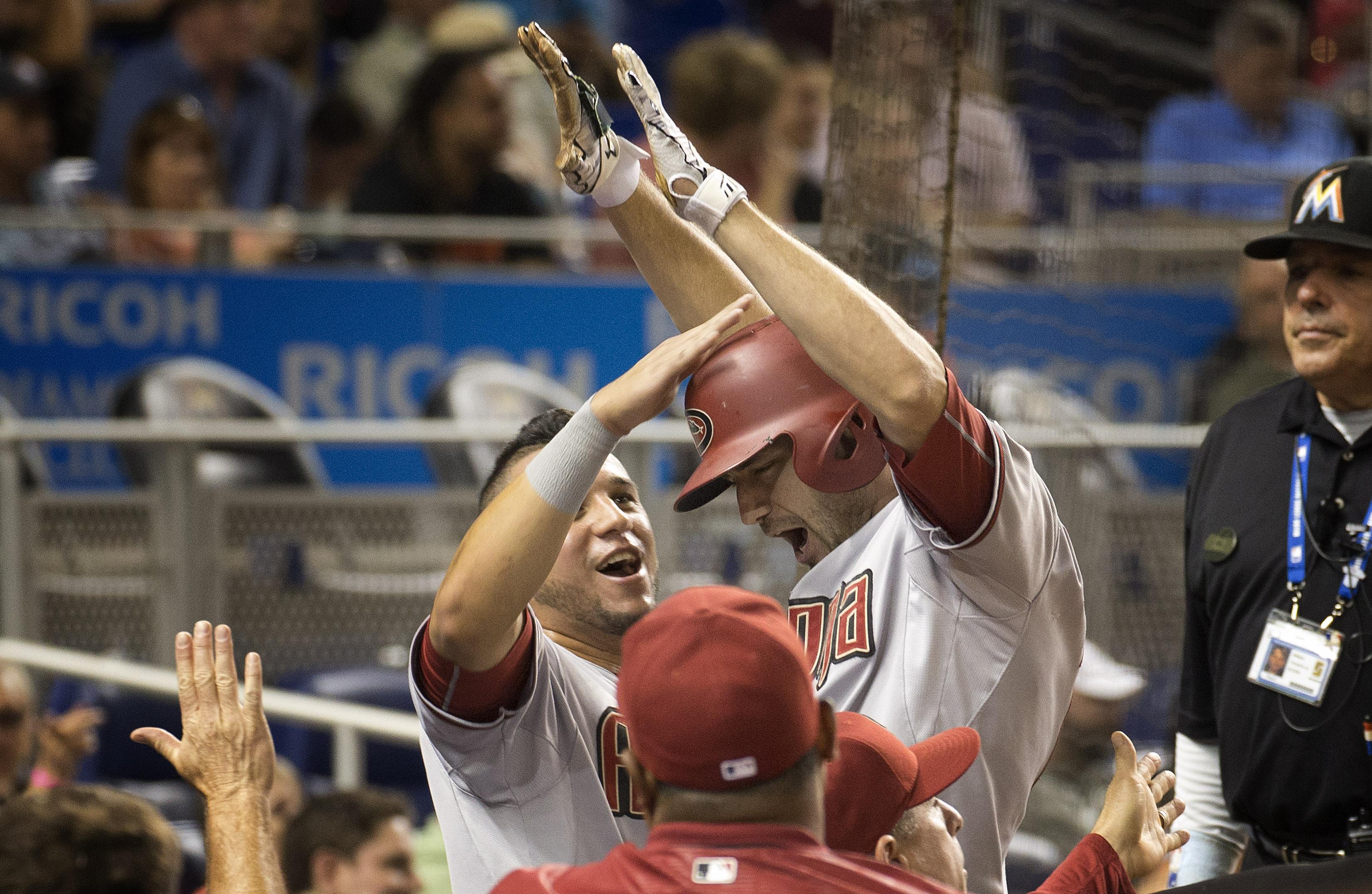 Arizona Diamondbacks'  David Peralta, left, celebrates with A.J. Pollock during the eighth inning of a baseball game against the Miami Marlins in Miami, Tuesday, May 19, 2015, after Pollock hit a go-ahead two-run home run. The Diamondbacks won 4-2. (AP Ph