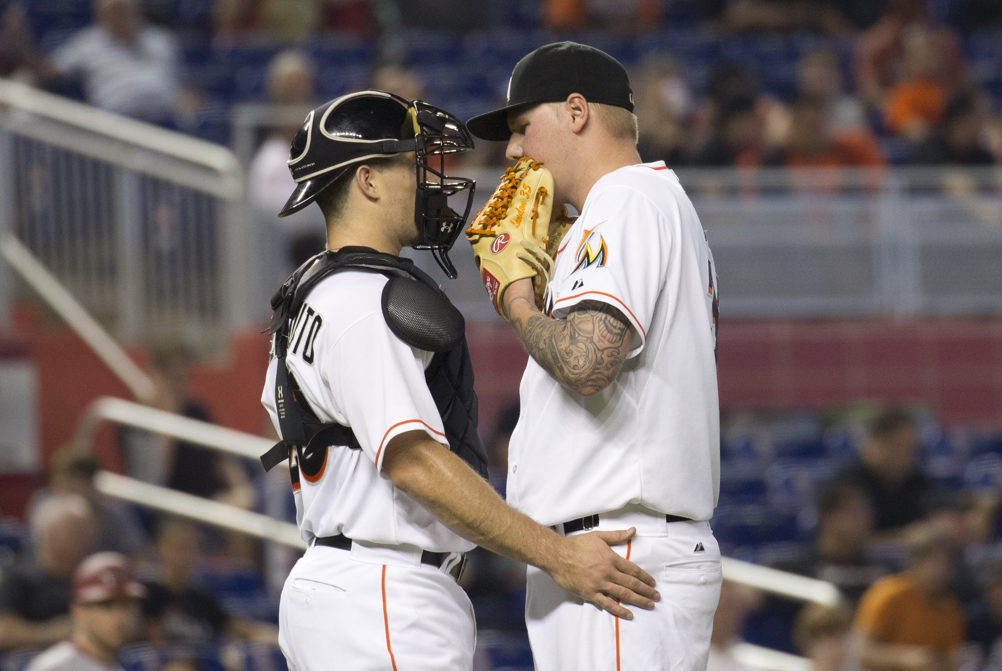 Miami Marlins catcher J.T. Realmuto (20) and Miami Marlins starting pitcher Mat Latos (35) have a mound conference during the fifth inning of a baseball game in Miami against the Arizona Diamondbacks, Thursday, May 21, 2015. The Diamondbacks won 7-6, swee