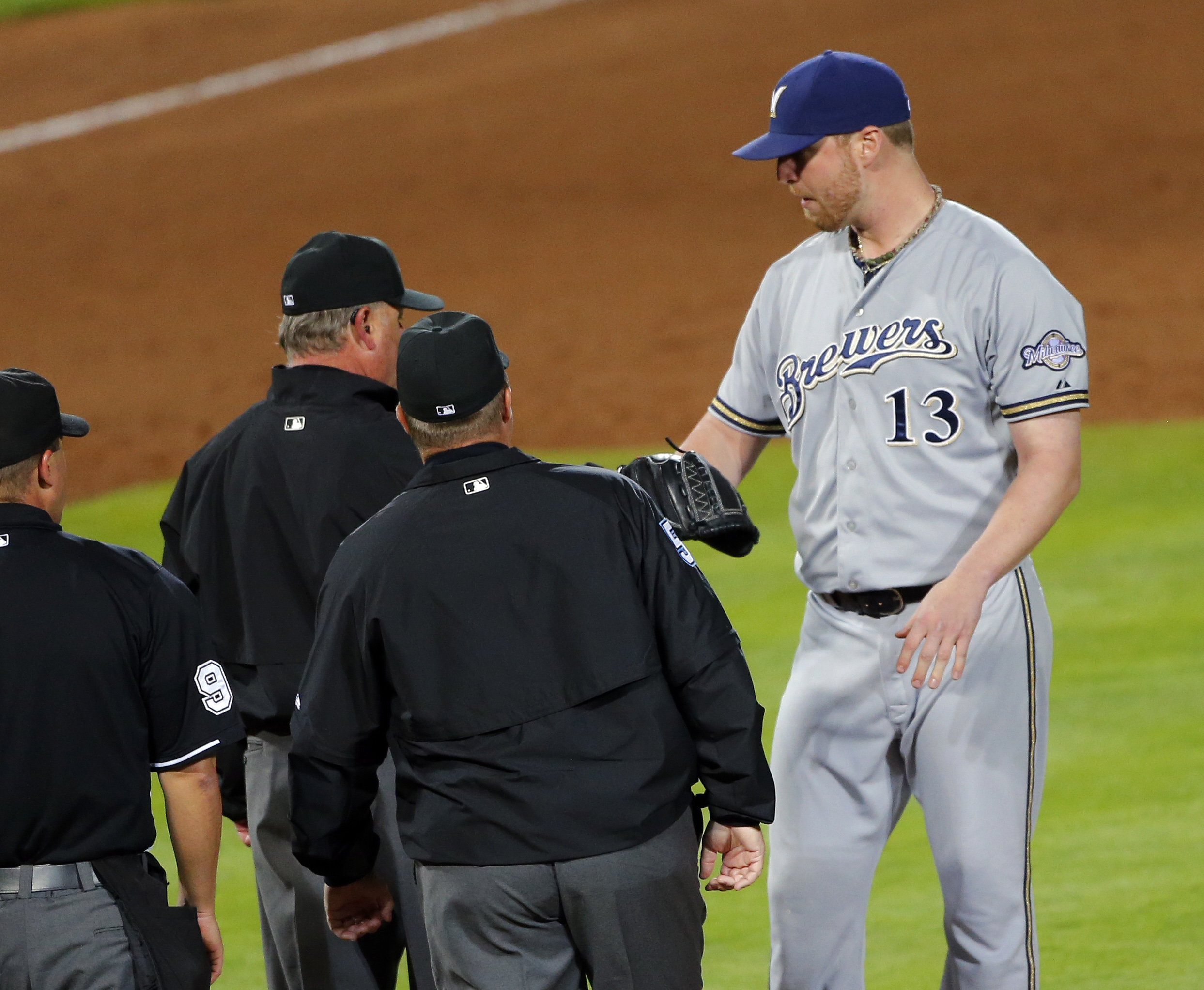 Milwaukee Brewers relief pitcher Will Smith (13) has his glove and arm examined by the umpiring crew before being ejected during the seventh inning of a baseball game against the Atlanta Braves on Thursday, May 21, 2015, in Atlanta. (AP Photo/John Bazemor