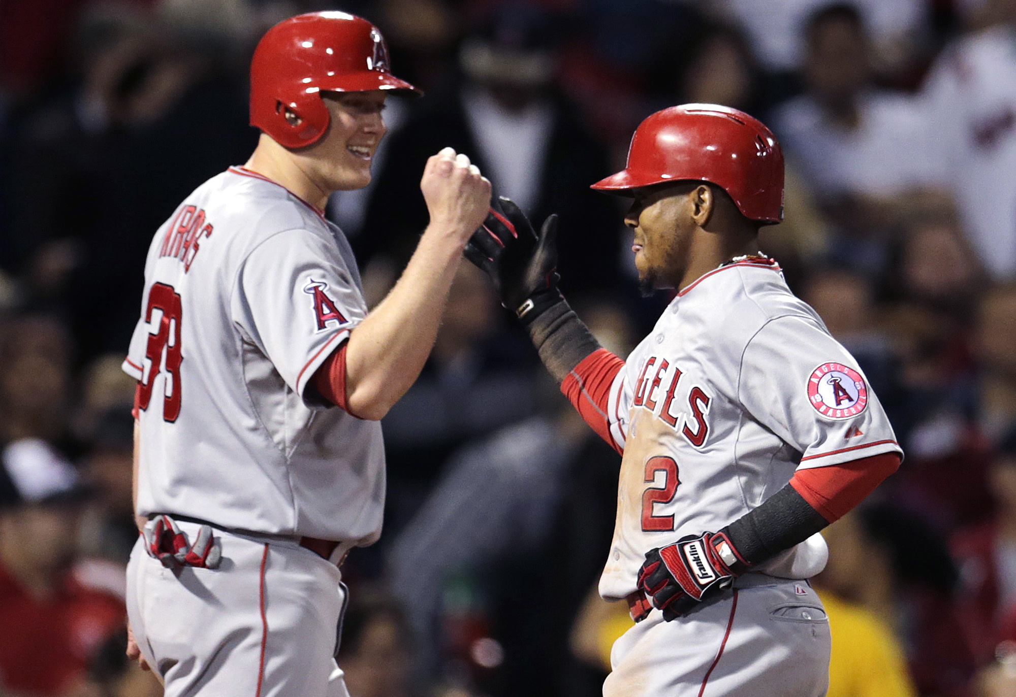 Los Angeles Angels' Erick Aybar is congratulated by teammate Marc Krauss after his two-run home run in the fifth inning of a baseball game against the Boston Red Sox at Fenway Park in Boston, Friday, May 22, 2015.  The Angels scored nine runs in the fifth