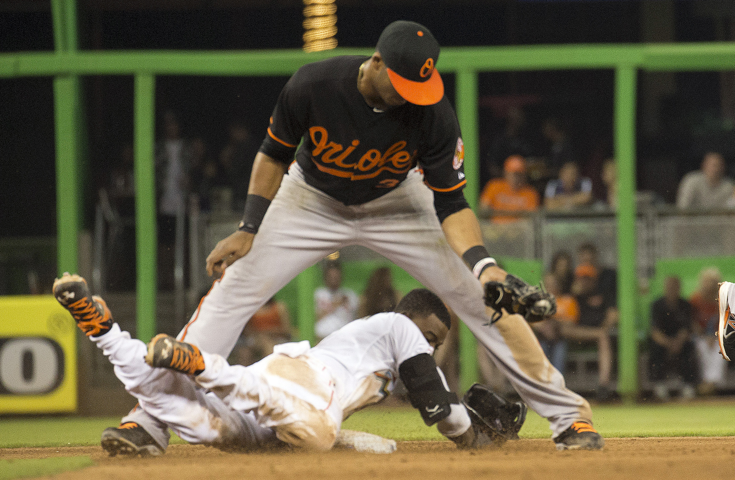 Miami Marlins' Dee Gordon, bottom, steals to second on a late throw to Baltimore Orioles' Jimmy Paredes, top, during the sixth inning of a baseball game in Miami, Friday, May 22, 2015. (AP Photo/J Pat Carter)