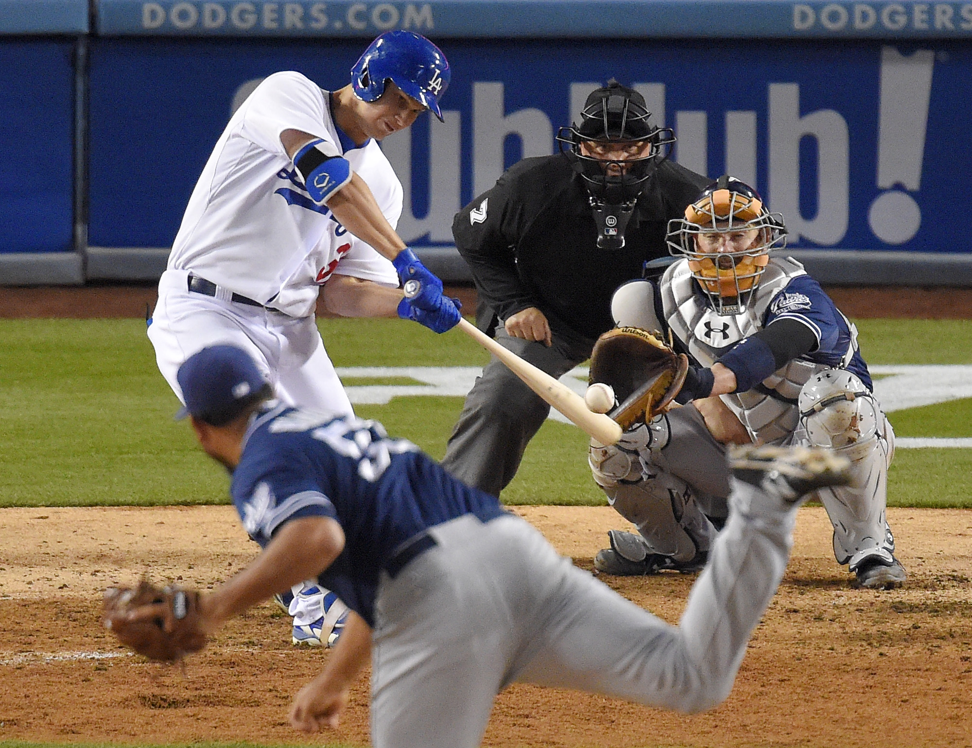 Los Angeles Dodgers' Joc Pederson, left, hits a solo home run off San Diego Padres relief pitcher Joaquin Benoit, in front of Padres catcher Derek Norris and home plate umpire Brian O'Nora during the eighth inning of a baseball game, Friday, May 22, 2015,