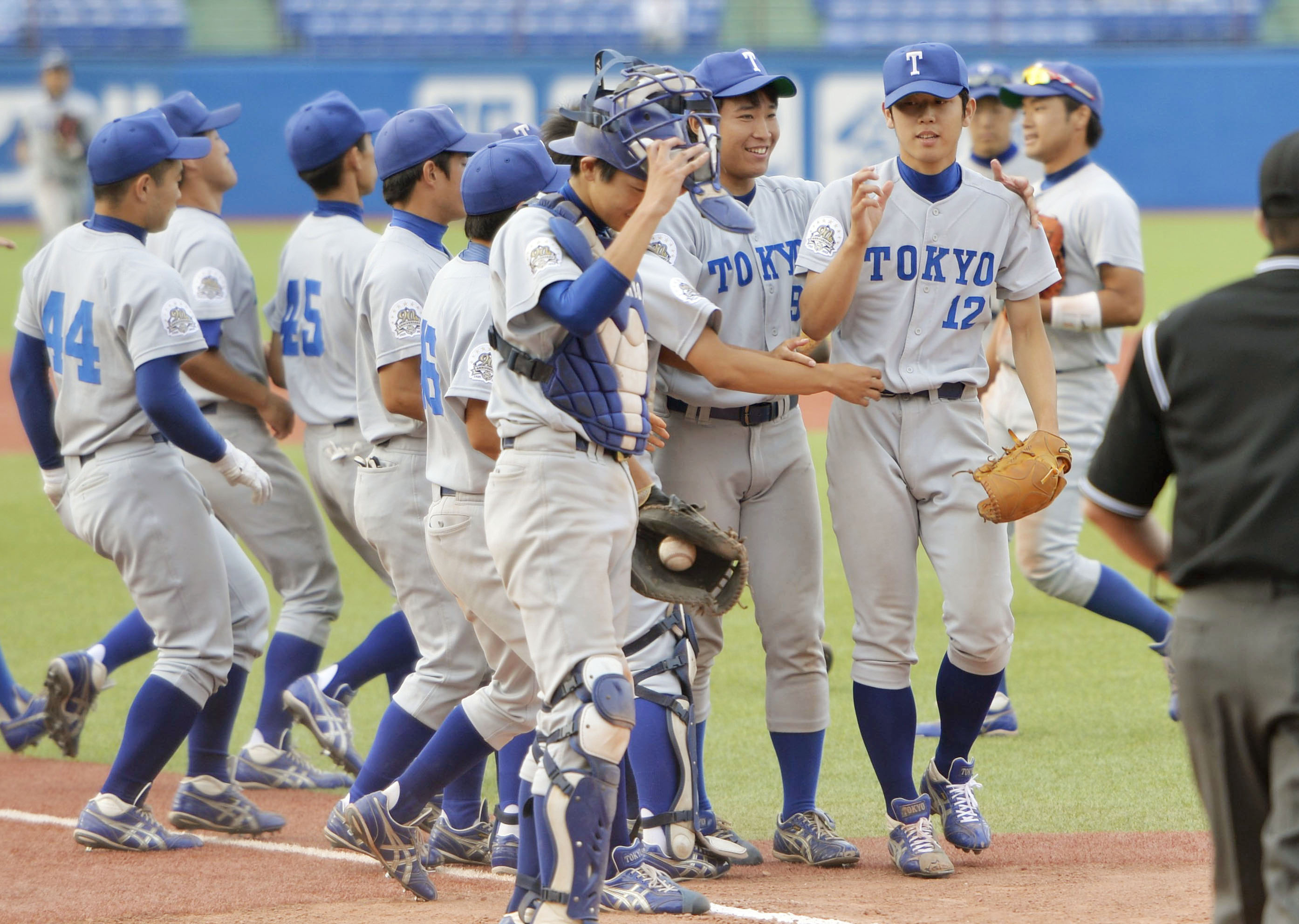 Pitcher Akihiro Shibata (12), right, of the University of Tokyo is congratulated by his teammates after putting an end to a record 94-game losing streak, winning for the first time in five years, during the Tokyo Big 6 Baseball League match against Hosei