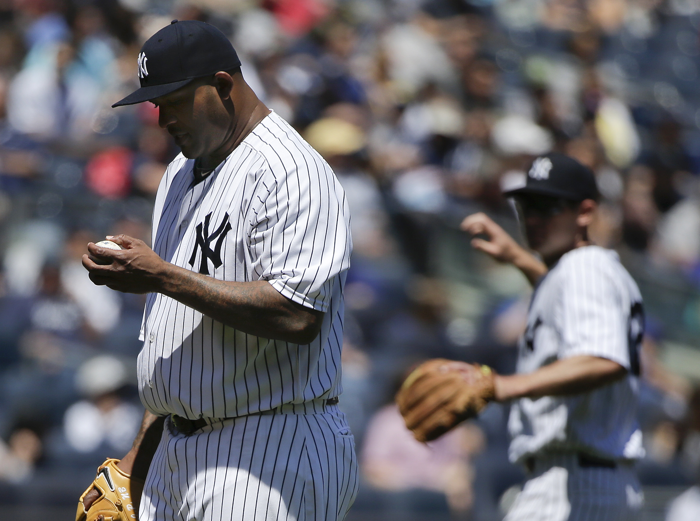 New York Yankees pitcher CC Sabathia checks the ball after giving up a hit to the Texas Rangers during the second inning of a baseball game Saturday, May 23, 2015, in New York. (AP Photo/Julie Jacobson)