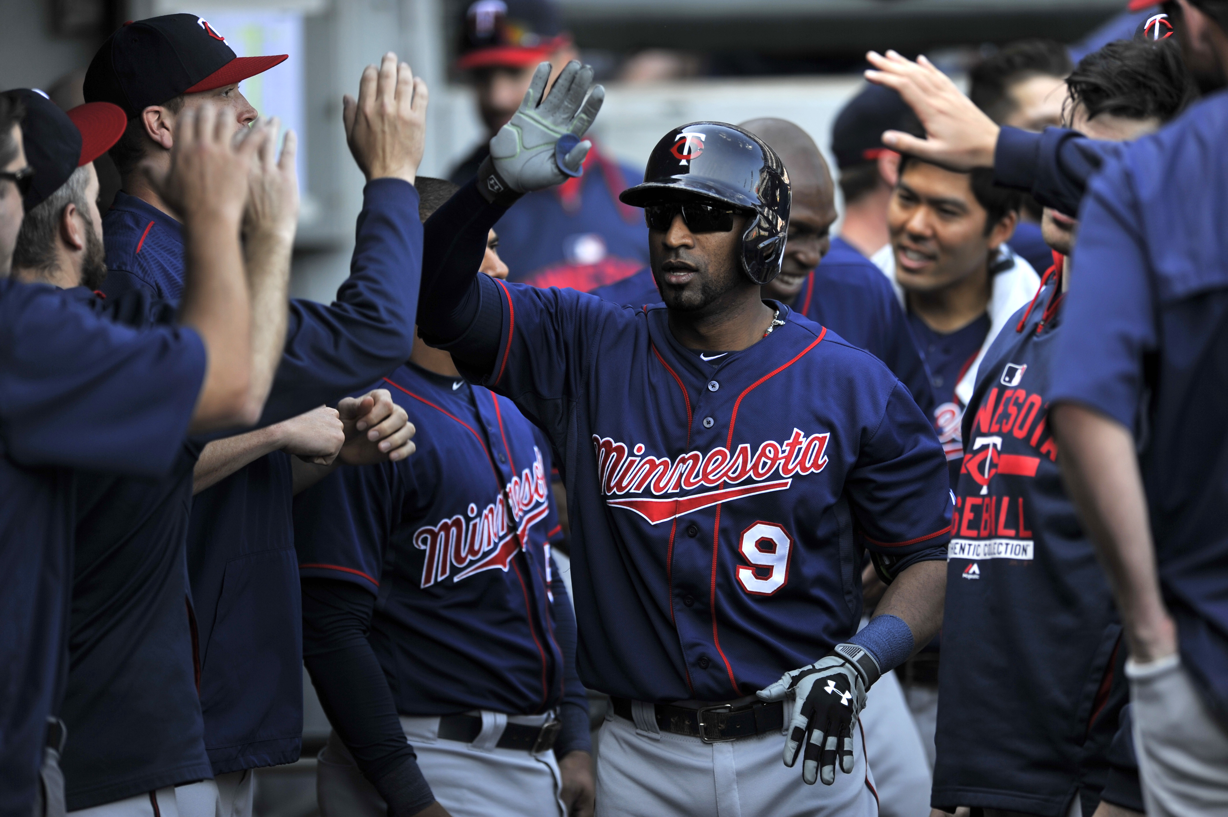 Minnesota Twins' Eduardo Nunez (9) celebrates with teammates in the dugout after hitting a solo home run during the second inning of a baseball game against the Chicago White Sox in Chicago, Saturday, May 23, 2015. (AP Photo/Paul Beaty)