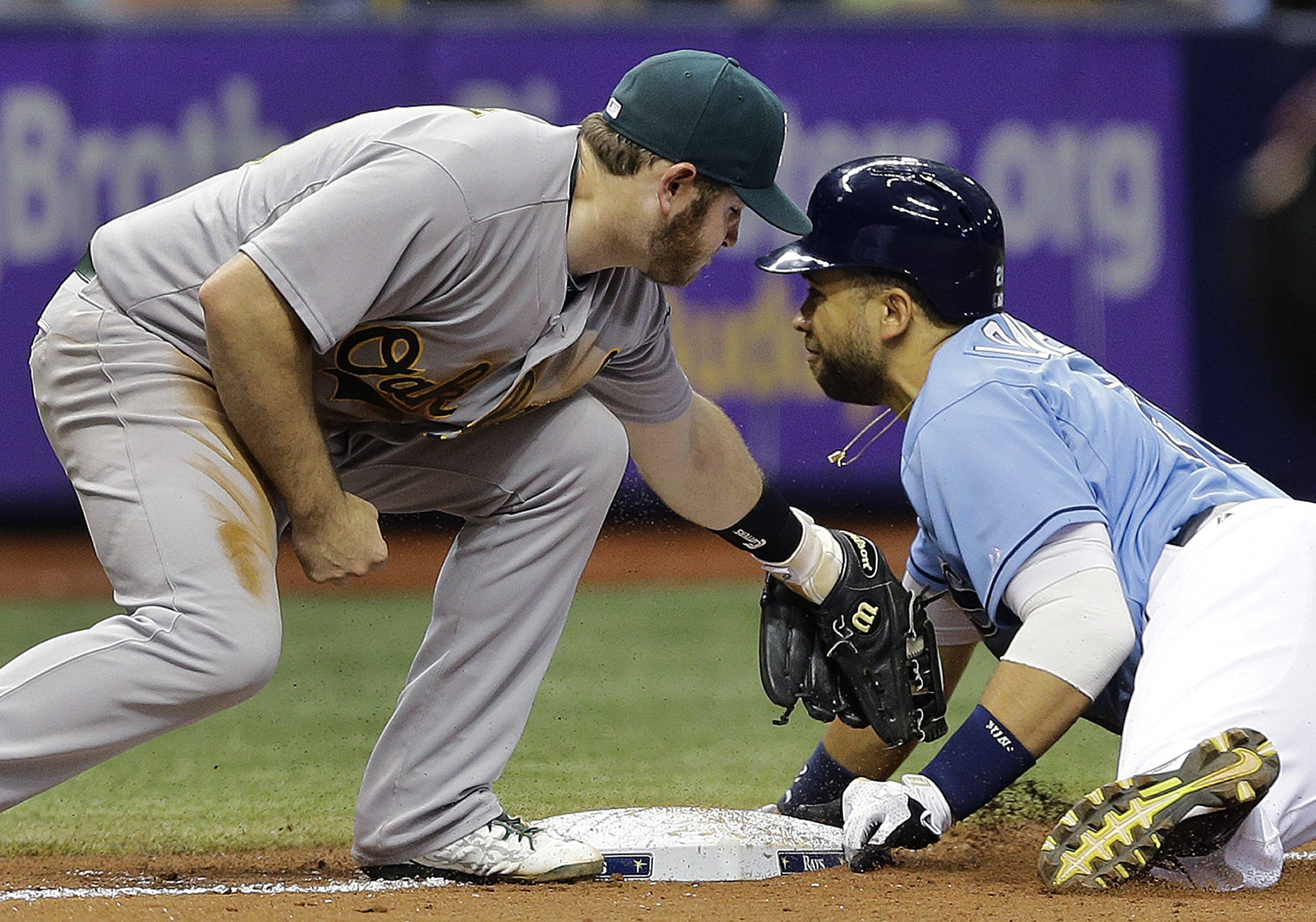 Tampa Bay Rays' James Loney, right, steals third base ahead of the tag by Oakland Athletics third baseman Max Muncy during the eighth inning of a baseball game Sunday, May 24, 2015, in St. Petersburg, Fla.  The A's won the game 7-2. (AP Photo/Chris O'Mear