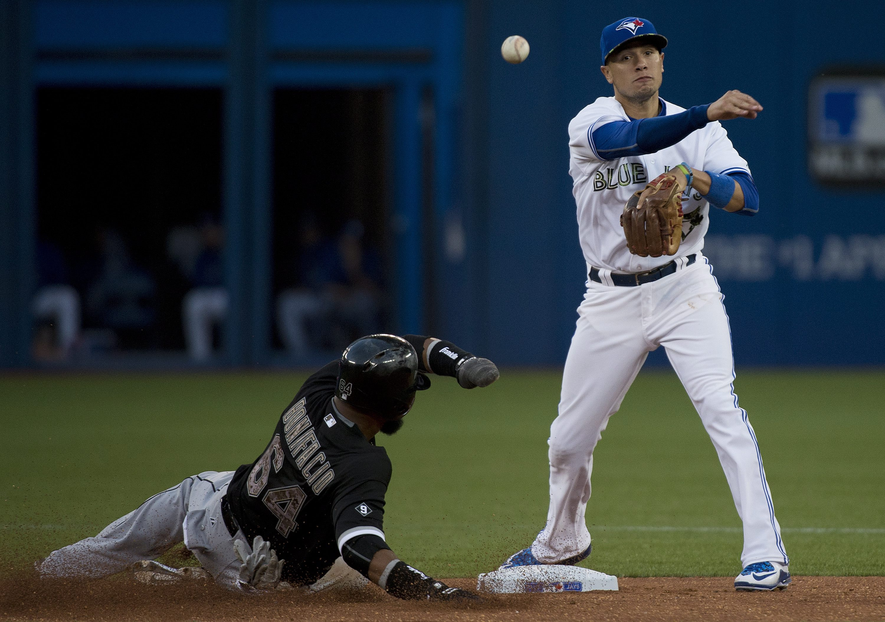 Toronto Blue Jays second baseman Ryan Goins, right, forces out Chicago White Sox's Emilio Bonifacio, left, then turns the double play over to first base to out White Sox's Gordon Beckham during sixth inning of a baseball game in Toronto, Ontario, Monday,