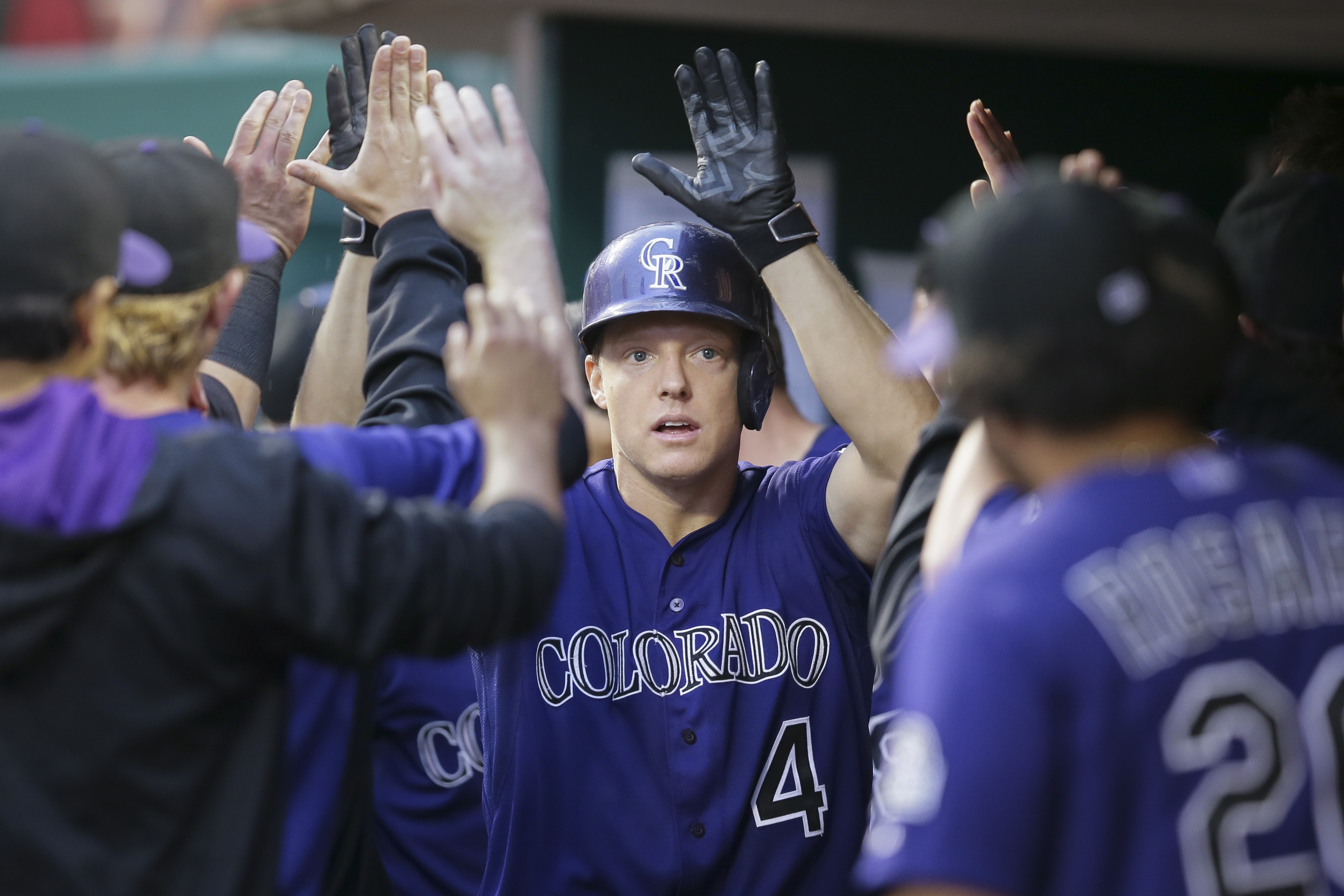 Colorado Rockies' Nick Hundley (4) celebrates in the dugout after hitting a solo home run in the fifth inning of a baseball game against the Cincinnati Reds, Tuesday, May 26, 2015, in Cincinnati. (AP Photo/John Minchillo)