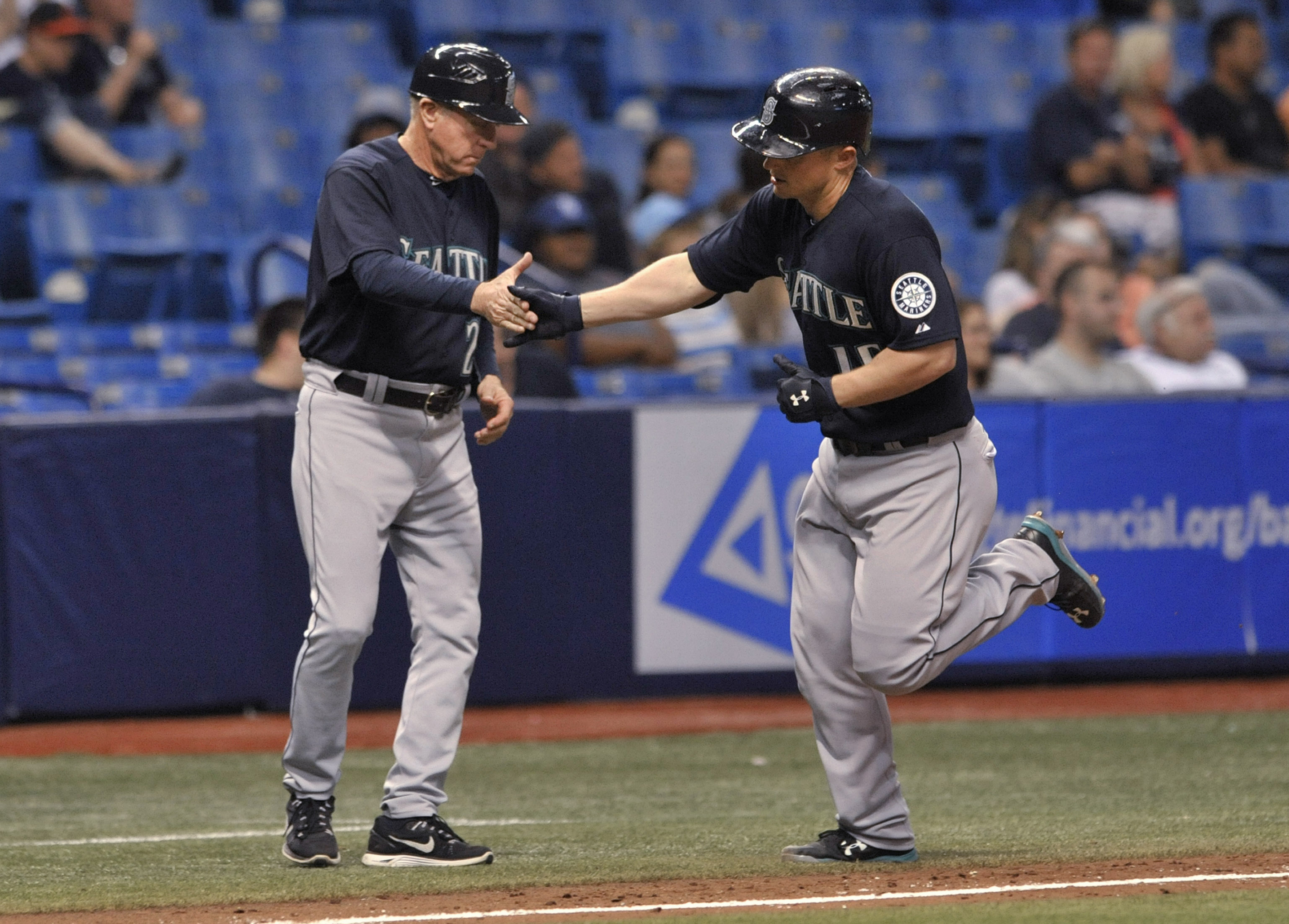 Seattle Mariners third base coach Rich Donnelly, left, congratulates Kyle Seager as he circles the bases after hitting a solo home run off Tampa Bay Rays reliever Brad Box Berger during the 10th inning of a baseball game Tuesday, May 26, 2015, in St. Pete