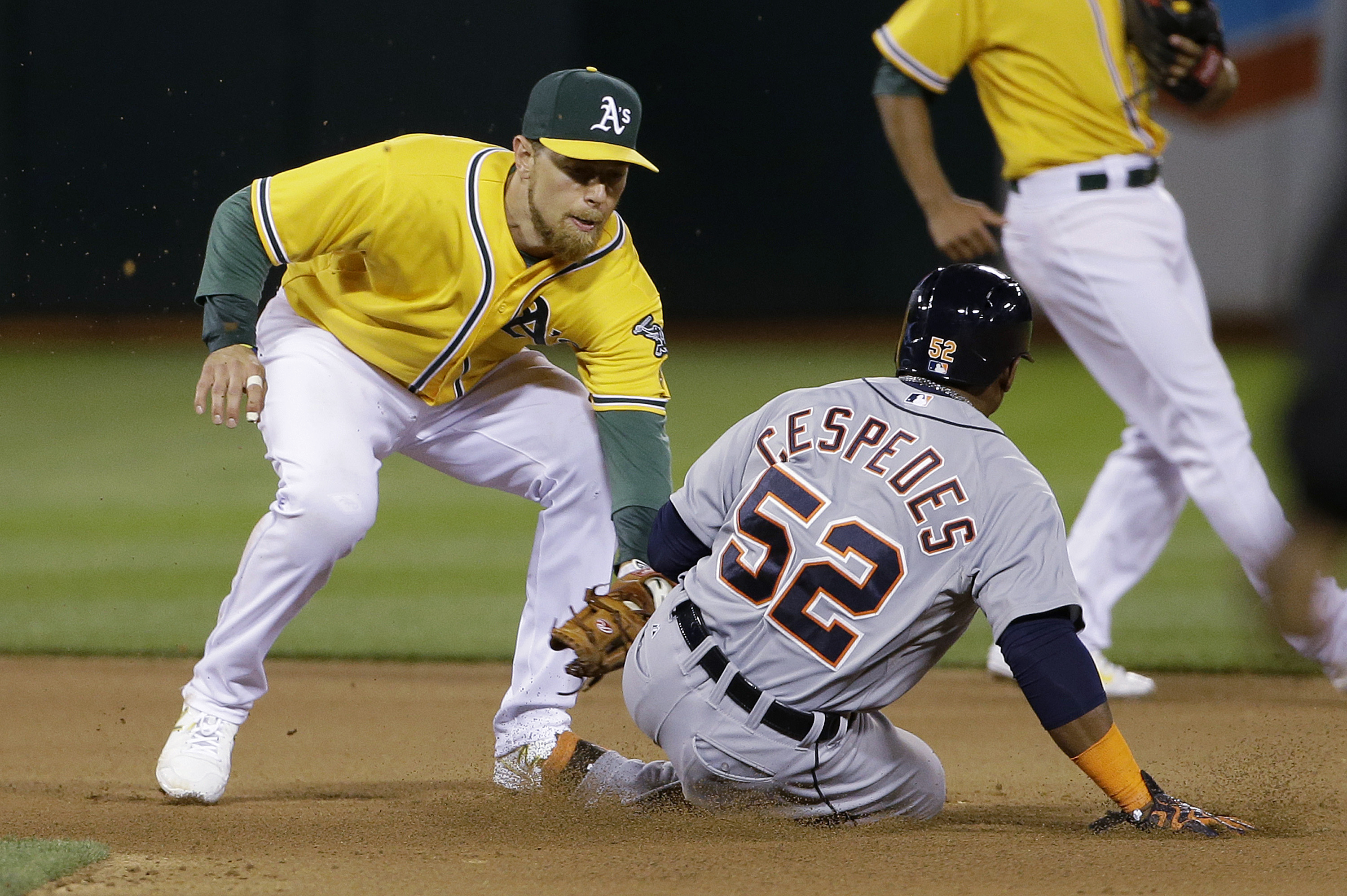 Detroit Tigers' Yoenis Cespedes (52) is tagged out trying to steal second base by Oakland Athletics second baseman Ben Zobrist during the seventh inning of a baseball game in Oakland, Calif., Tuesday, May 26, 2015. (AP Photo/Jeff Chiu)