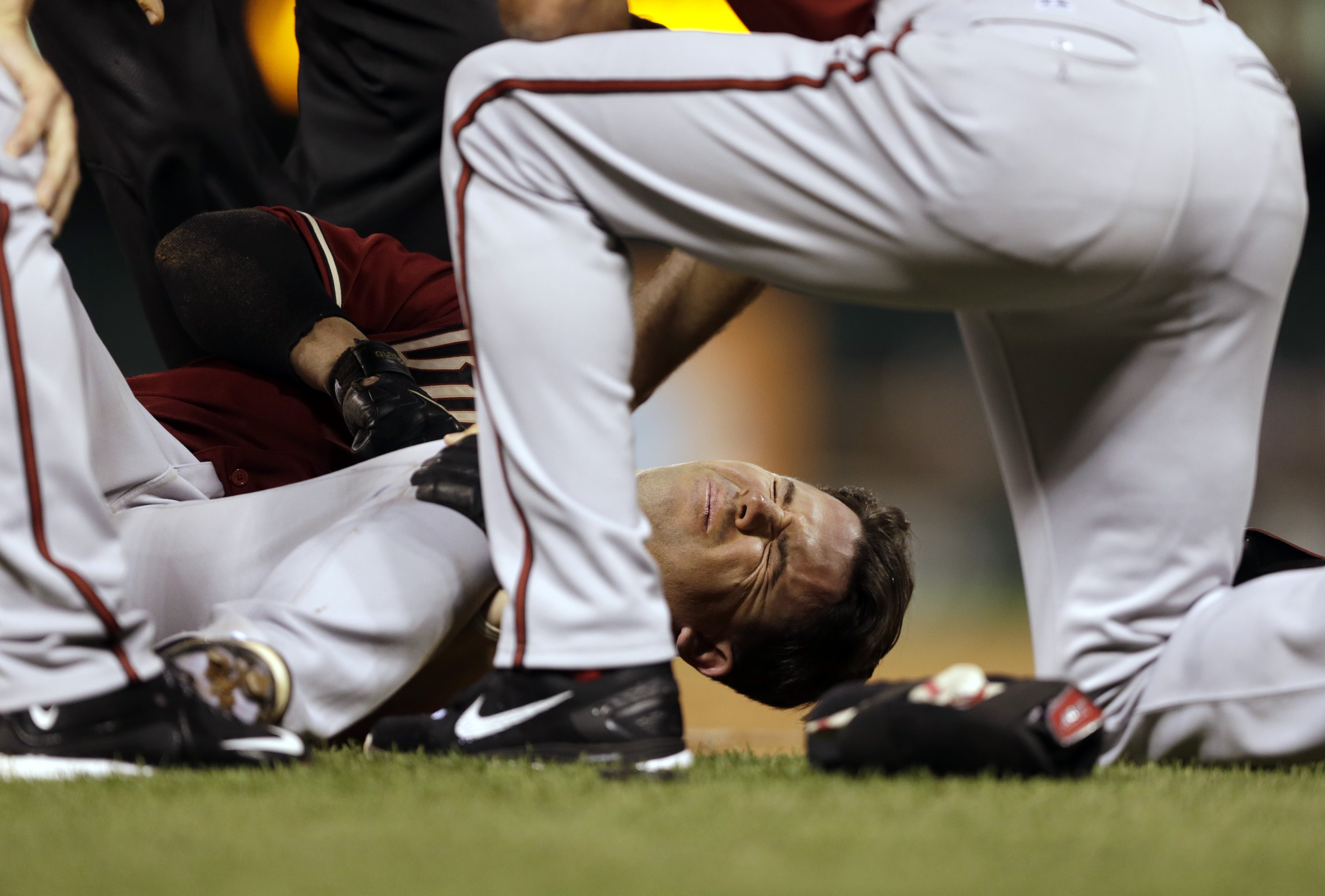 Arizona Diamondbacks' Tuffy Gosewisch holds his leg as he is tended to by teammates after being injured running out a ground out during the sixth inning of a baseball game against the St. Louis Cardinals Wednesday, May 27, 2015, in St. Louis. Gosewisch le