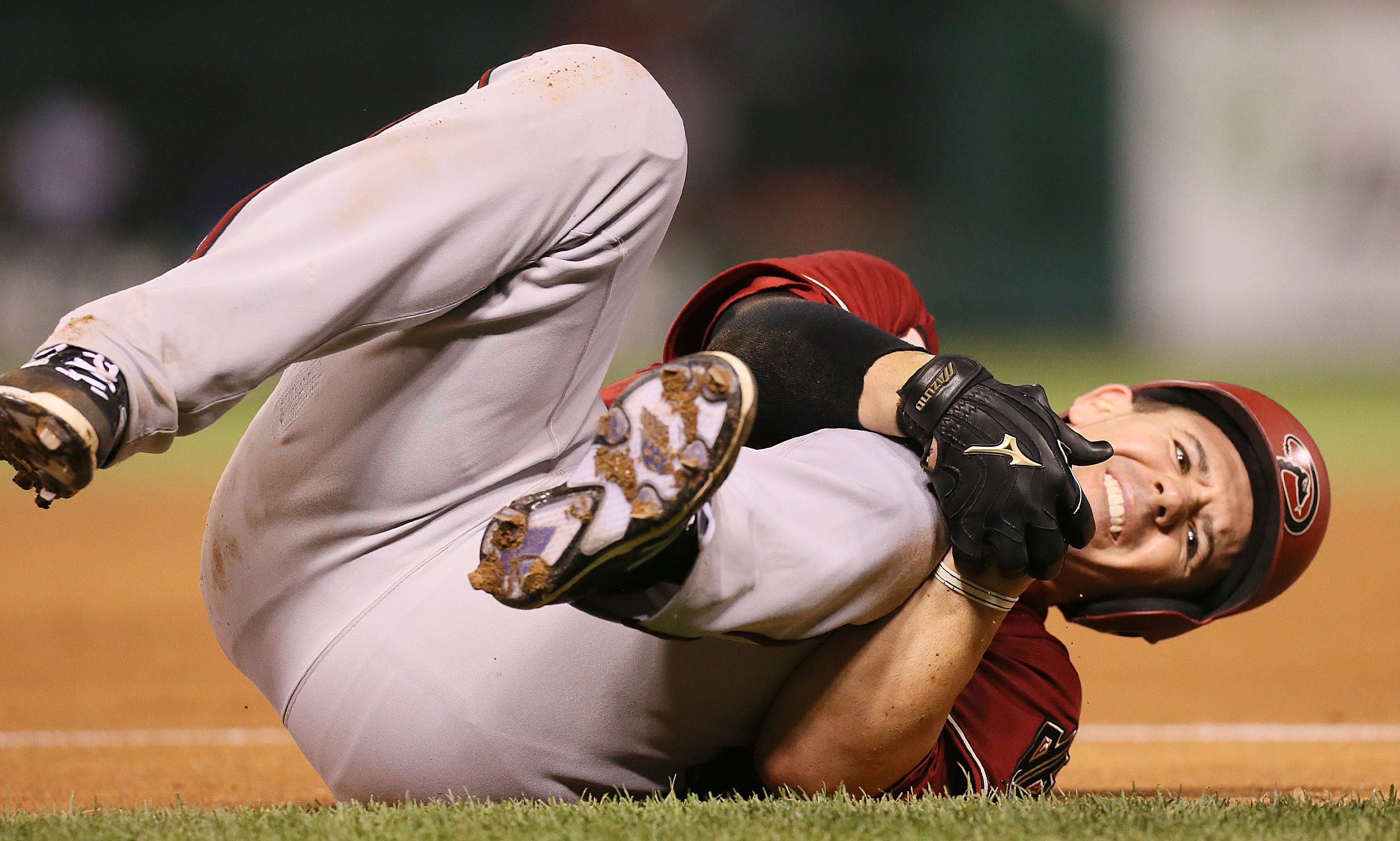 Arizona Diamondbacks' Tuffy Gosewisch clutches his left knee after being injured running out a ground out in sixth inning action during a game between the St. Louis Cardinals and the Arizona Diamondbacks on Wednesday, May 27, 2015, at Busch Stadium in St.