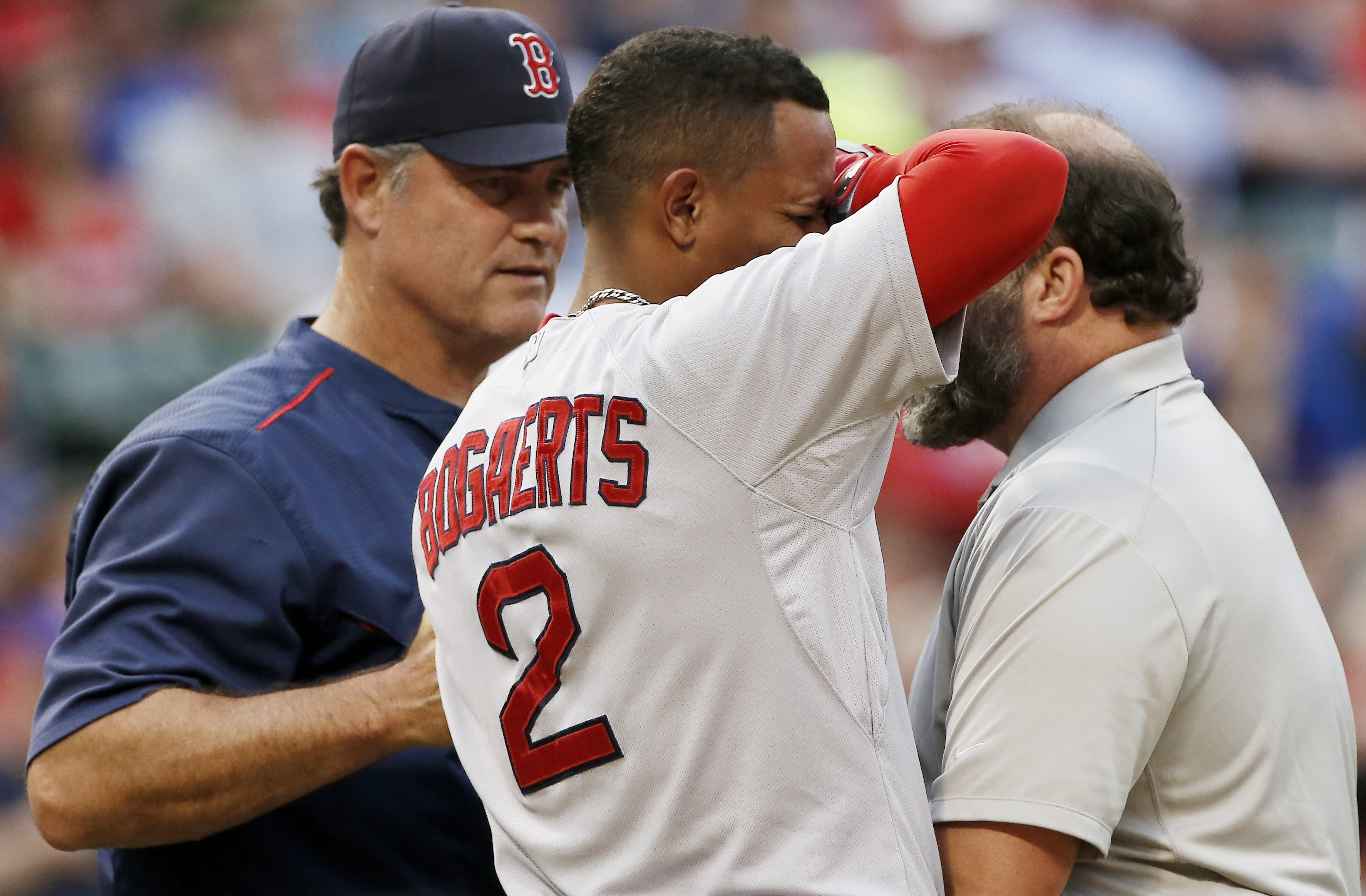Boston Red Sox Xander Bogaerts (2) is tended to by manager John Farrell, left, and a trainer after being hit by a pitch in the left wrist during the second inning of a baseball game against the Texas Rangers, Thursday, May 28, 2015, in Arlington, Texas. (