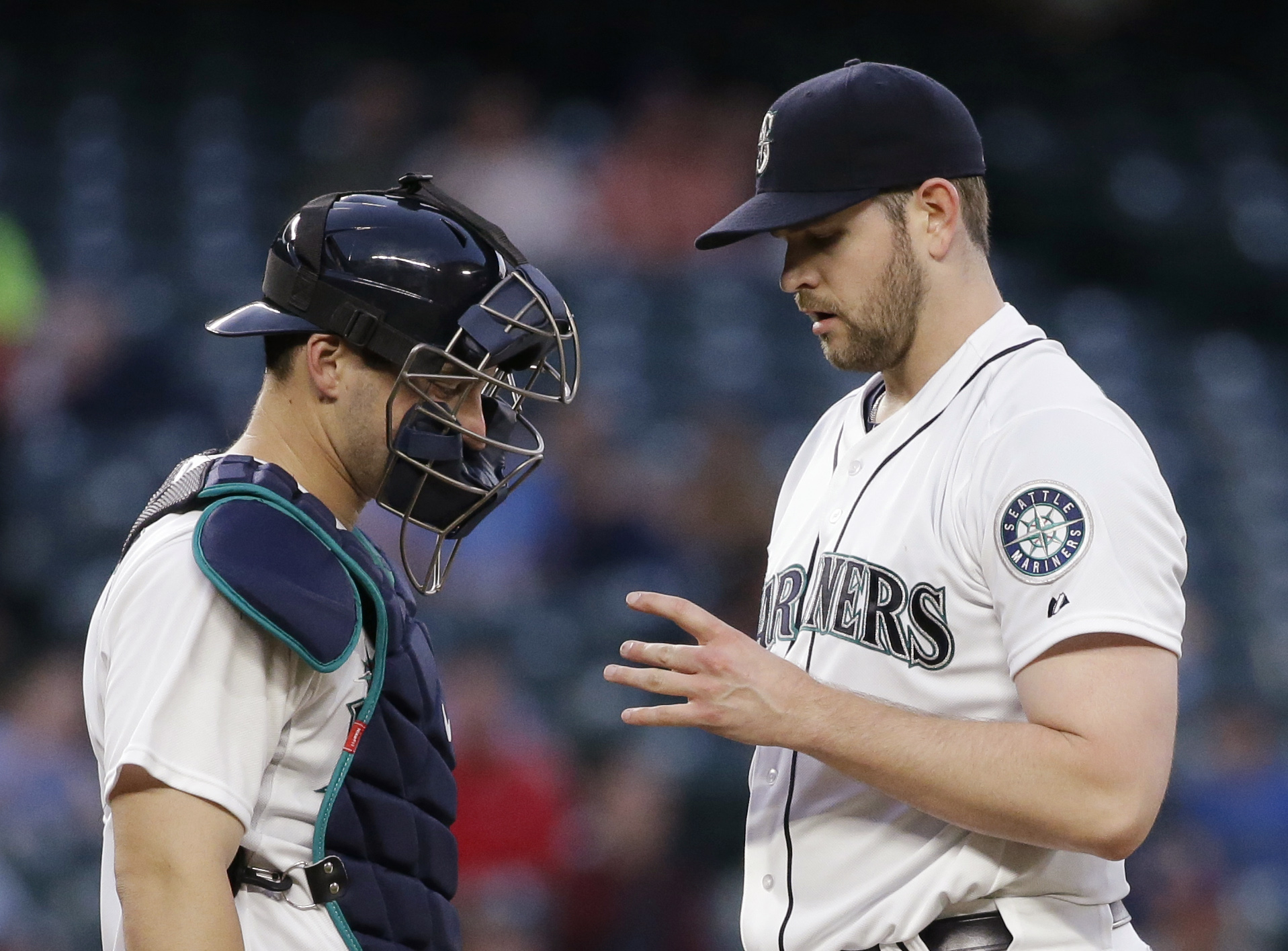 Seattle Mariners catcher Mike Zunino, left, and starting pitcher James Paxton looks at Paxton's pitching hand in the fifth inning of a baseball game againdy the Cleveland Indians on Thursday, May 28, 2015, in Seattle. Paxton came out of the game. (AP Phot