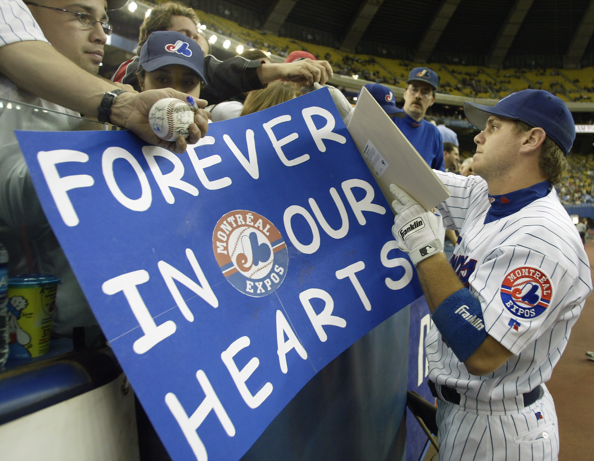FILE - In this Sept. 29, 2004, file photo, Montreal Expos first baseman Brad Wilkerson signs autographs before the team's final home game against the Florida Marlins in Montreal. The team moved to Washington, D.C., the following season after 35 years in M