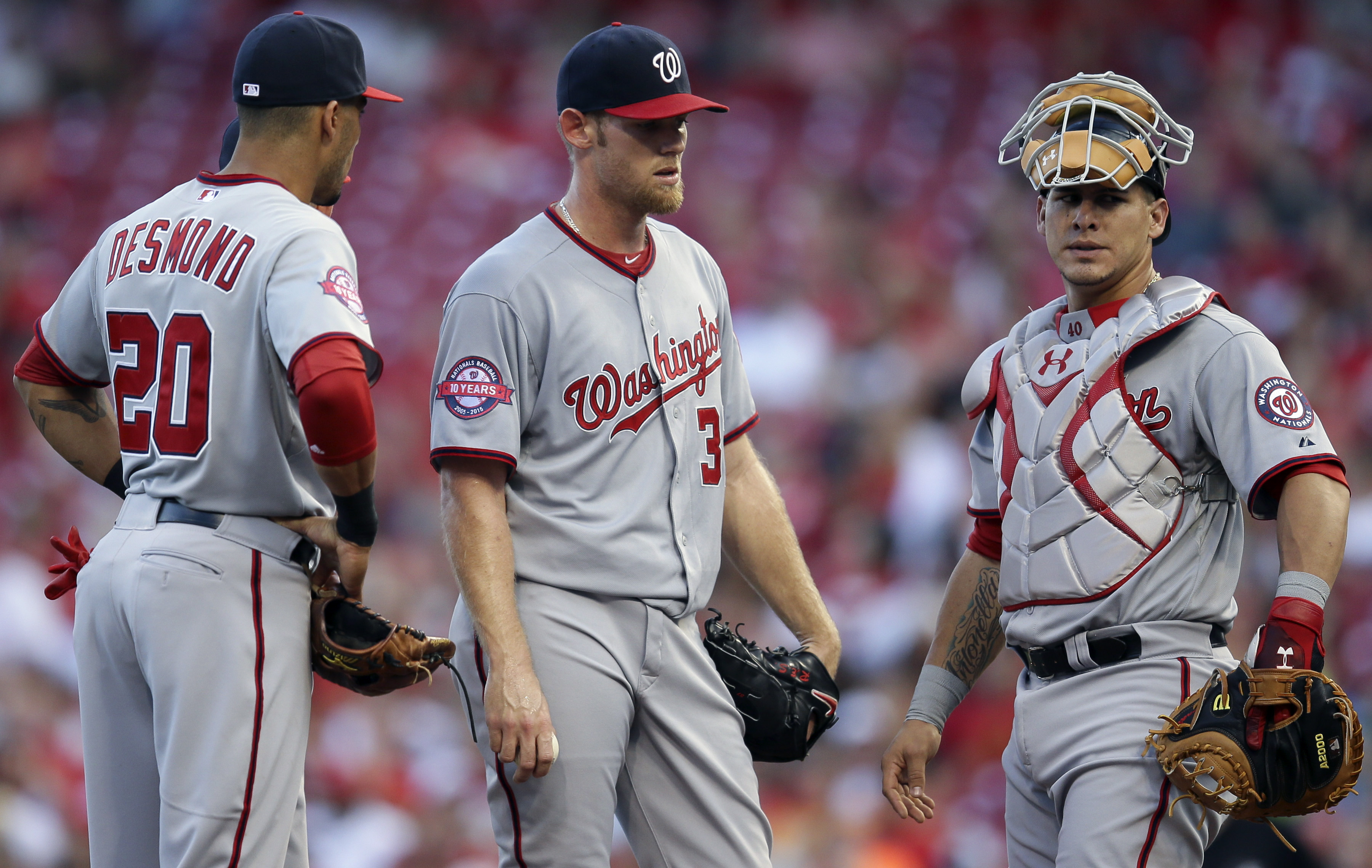 Washington Nationals starting pitcher Stephen Strasburg, center, stands on the mound alongside shortstop Ian Desmond (20) and catcher Wilson Ramos in the second inning of a baseball game against the Cincinnati Reds, Friday, May 29, 2015, in Cincinnati. (A
