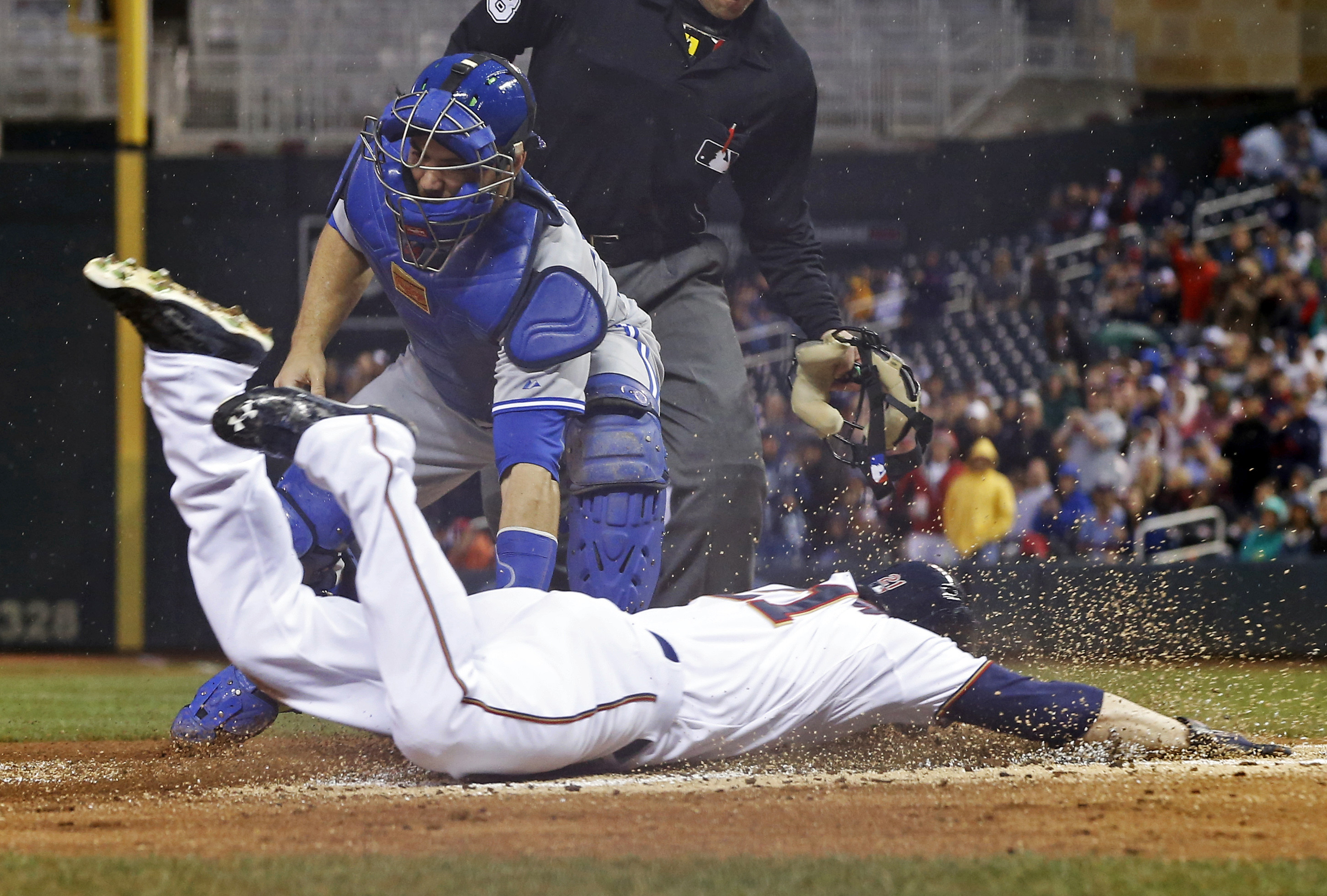 Minnesota Twins' Shane Robinson, bottom, beats the tag by Toronto Blue Jays catcher Russell Martin to score on a hit by Torii Hunter off Mark Buehrle in the first inning of a baseball game, Friday, May 29, 2015, in Minneapolis. (AP Photo/Jim Mone)