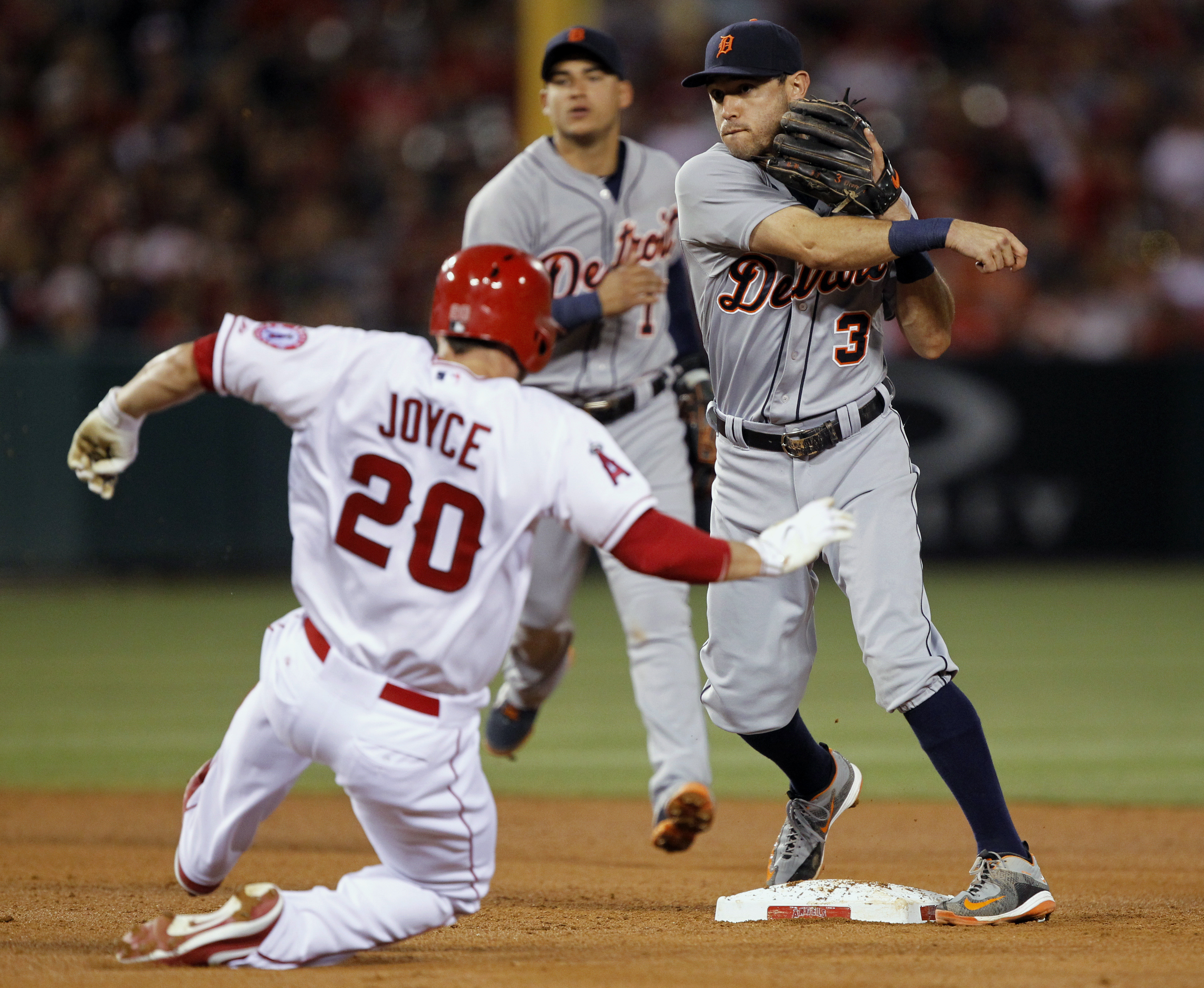 Detroit Tigers second baseman Ian Kinsler (3) makes the relay to first over Los Angeles Angels' Matt Joyce (20), to get the Angels' Chris Iannetta at first or a double play, with shortstop Jose Iglesias watching, during the fourth inning of a baseball gam