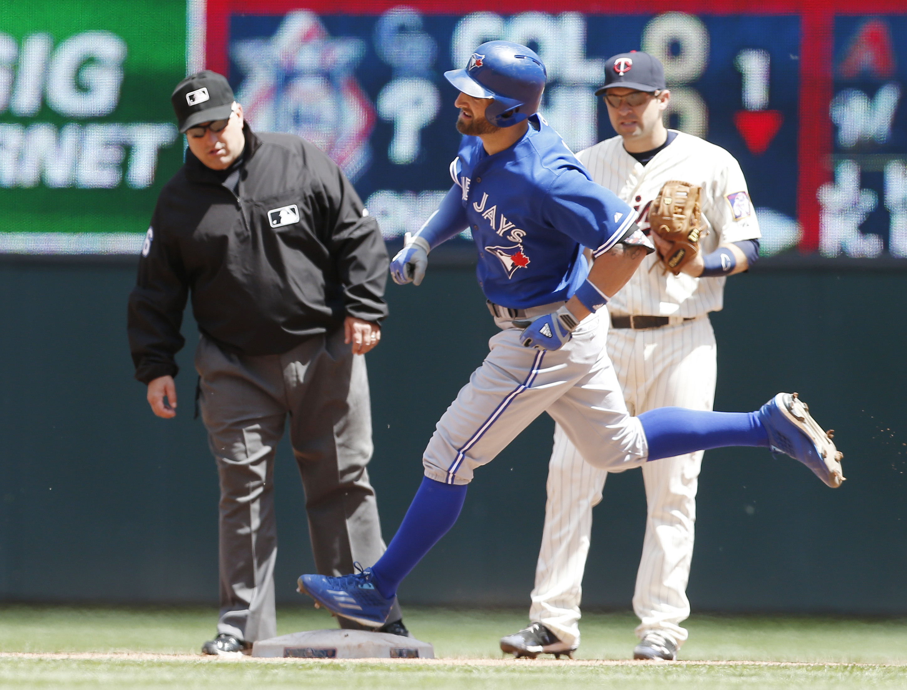 Toronto Blue Jays' Kevin Pillar, center, runs past Minnesota Twins second baseman Brian Dozier and second base umpire Eric Cooper, left, as he rounds the bases after hitting a solo home run off Twins pitcher Kyle Gibson in the fourth inning of a baseball