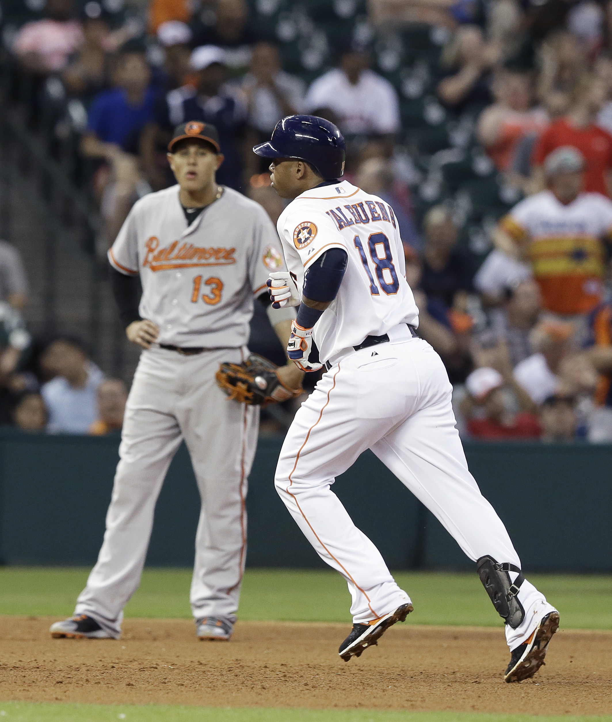 Houston Astros' Luis Valbuena (18) rounds the bases in front of Baltimore Orioles third baseman Manny Machado (13) on a solo homer in the fifth inning of a baseball game Monday, June 1, 2015, in Houston. (AP Photo/Pat Sullivan)