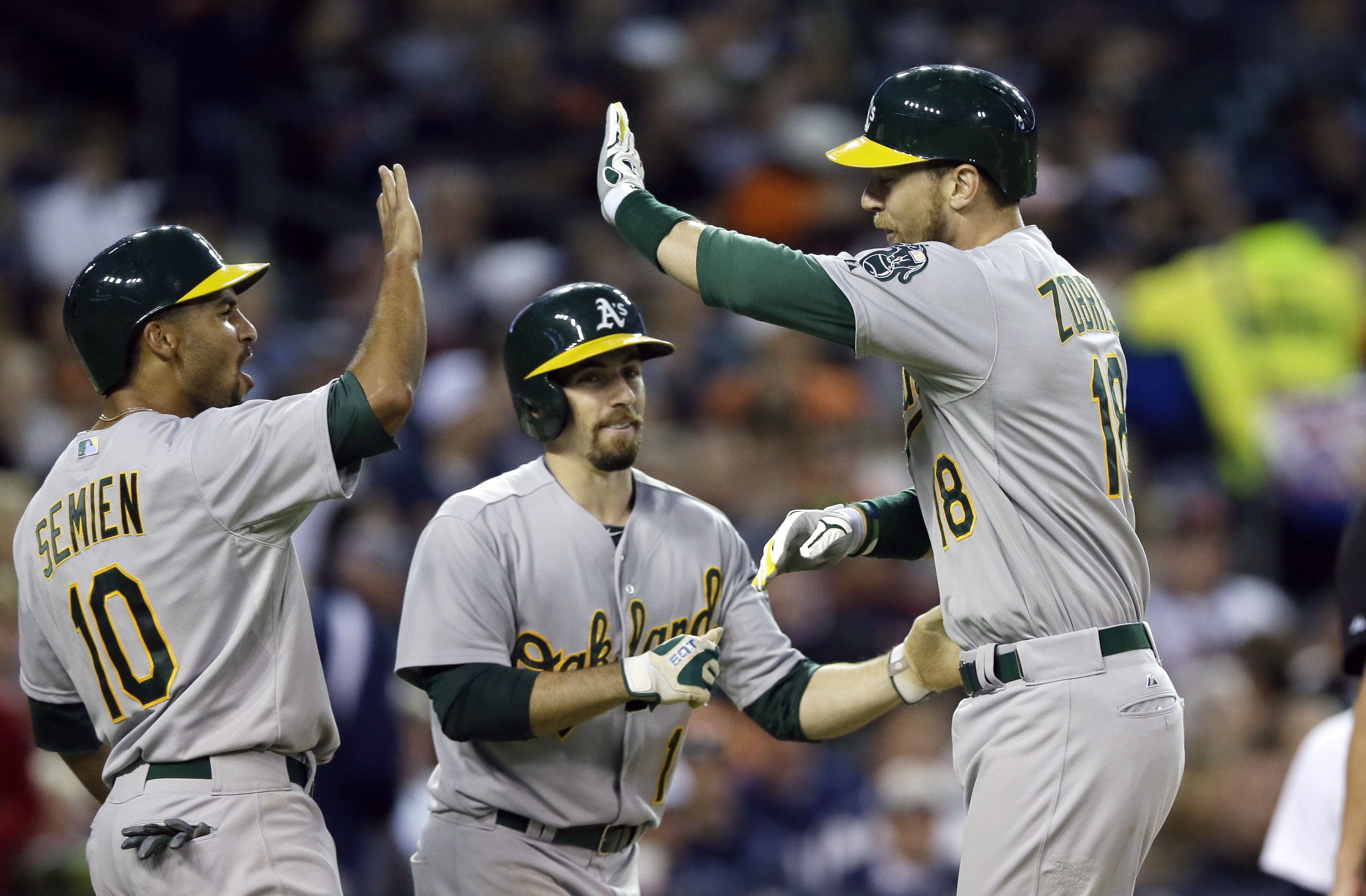 Oakland Athletics' Ben Zobrist, right, is greeted by teammates Marcus Semien (10) and Billy Burns after they scored on the grand slam by Zobrist off Detroit Tigers relief pitcher Angel Nesbitt during the seventh inning of a baseball game, Tuesday, June 2,