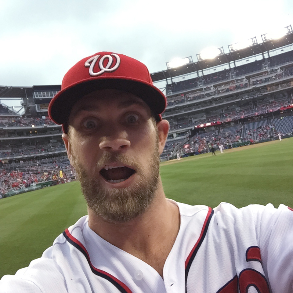 Washington Nationals outfielder Bryce Harper takes a photo of himself with a cell phone tossed to him by fan Jamie Roach, Tuesday, June 2, 2015, at Nationals Park in Washington. Roach noticed Harper gesturing for her picture-taking cell phone before the s