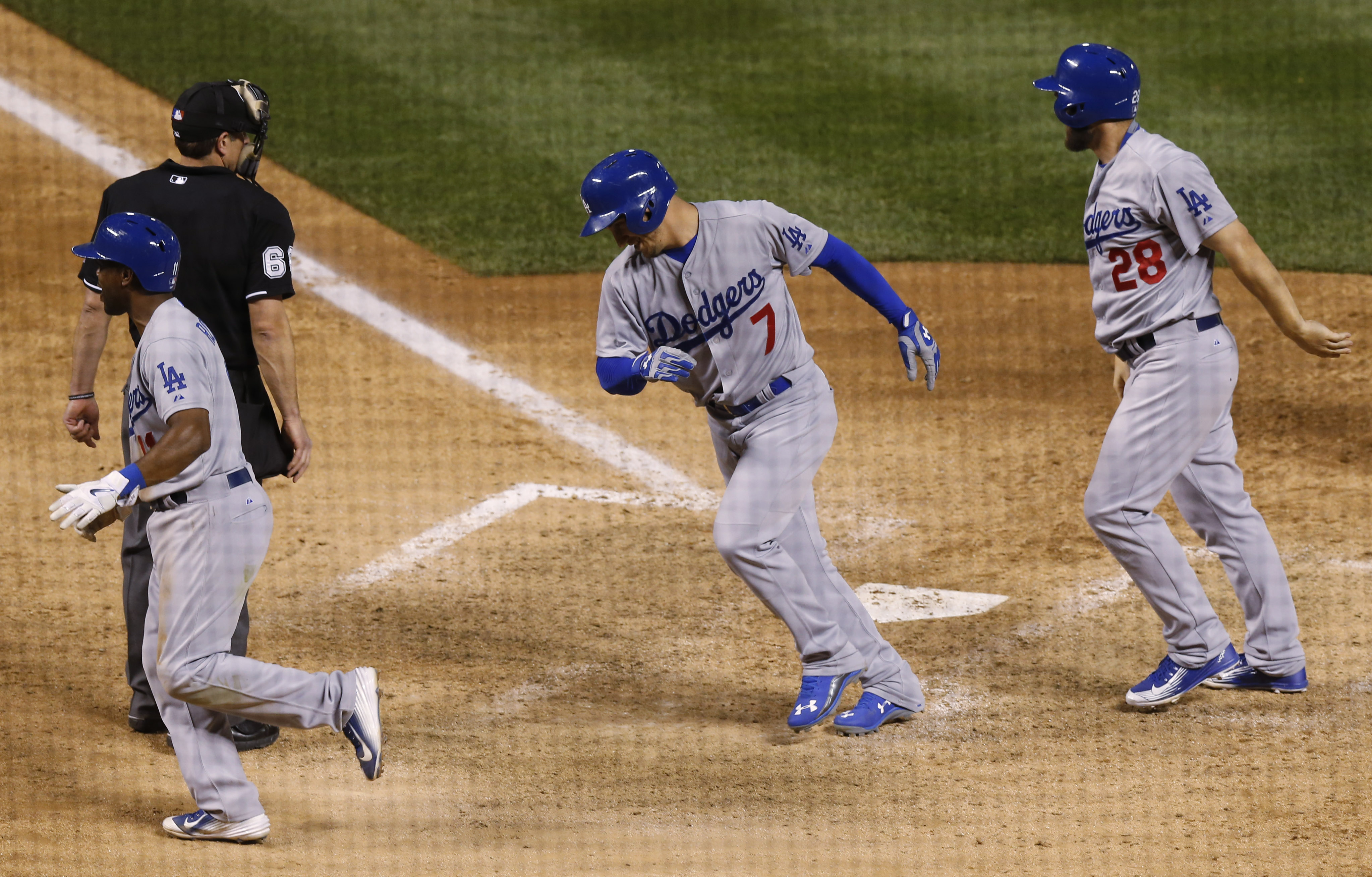 Los Angeles Dodgers' Alex Guerrero, center, celebrates his grand slam with teammates Jimmy Rollins, left, and Chris Heisey in the ninth inning off Colorado Rockies relief pitcher Rafael Betancourt in Game 2 of a baseball doubleheader Tuesday, June 2, 2015