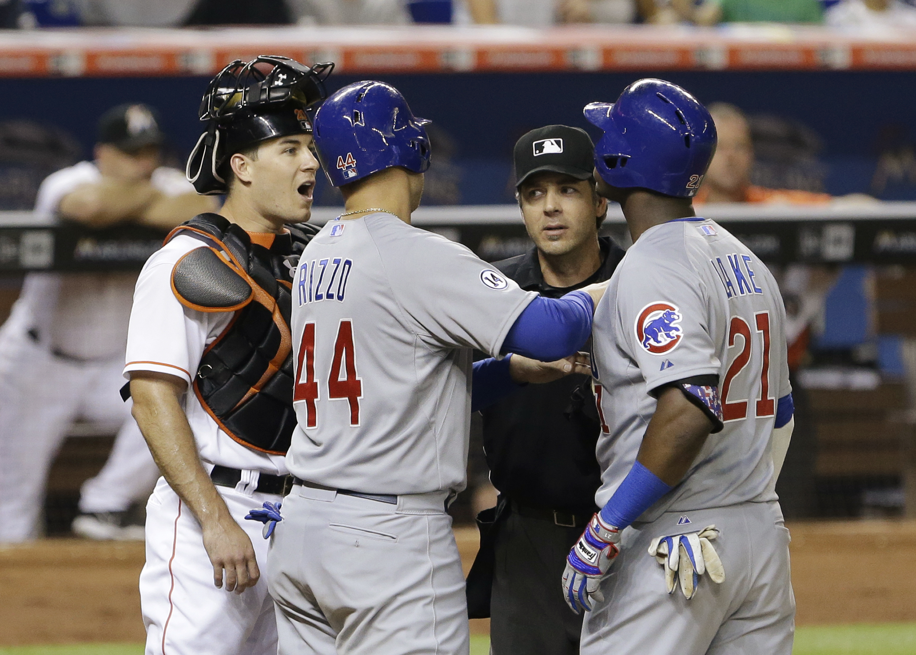 Chicago Cubs' Anthony Rizzo (44) and home plate umpire James Hoye, second from right, hold back Junior Lake (21) as Lake and Miami Marlins catcher J.T. Realmuto, left, exchange words after Lake hit a home run scoring Rizzo during the sixth inning of a bas