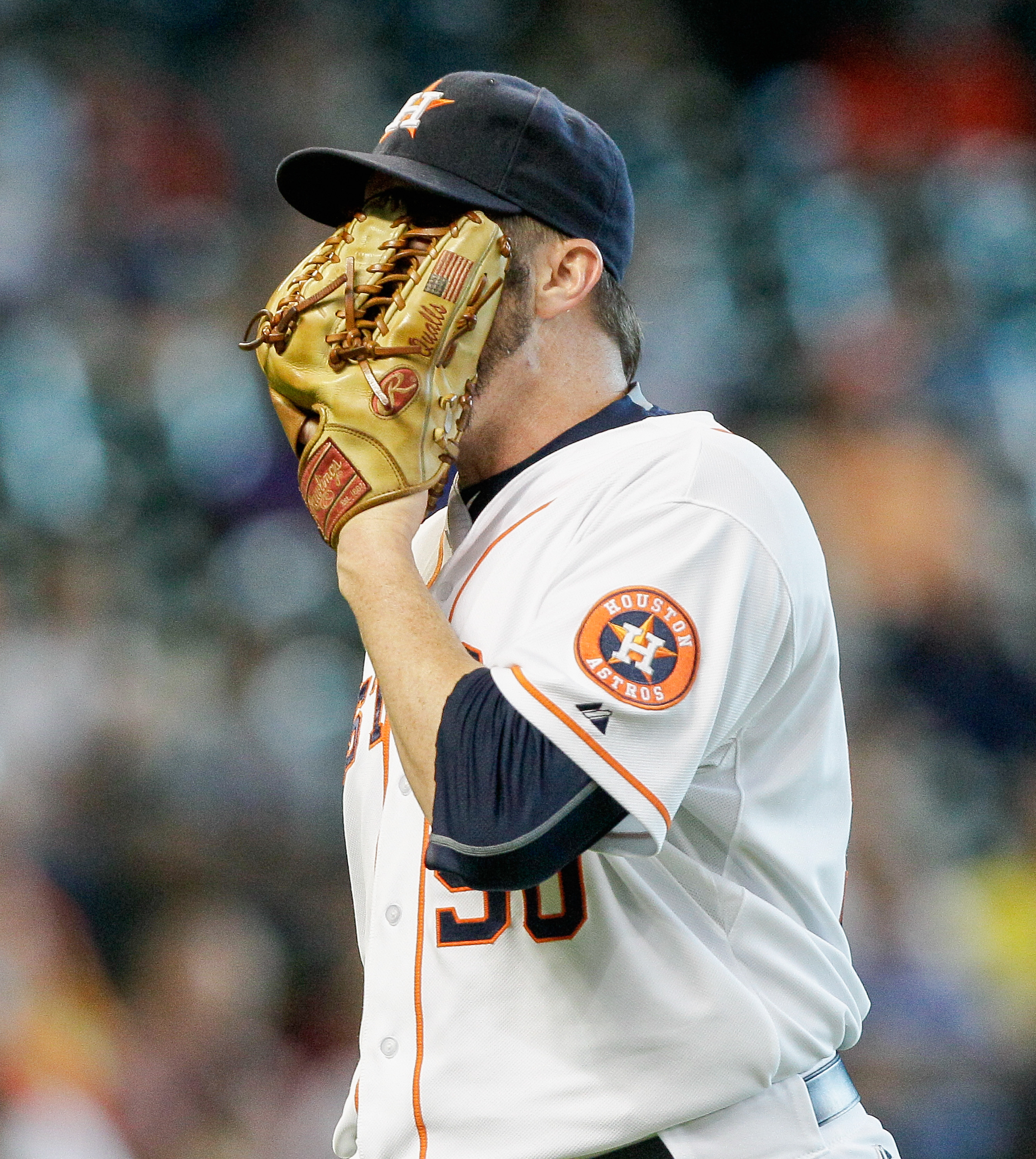 Houston Astros' Chad Qualls buries his face in his glove after giving up a home run to Baltimore Orioles' Adam Jones in the eighth inning of a baseball game, Thursday, June 4, 2015 in Houston. (AP Photo/Bob Levey)