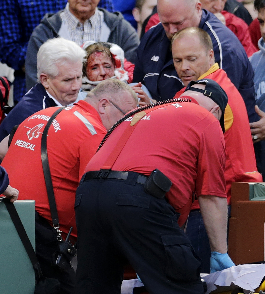 RETRANSMISSION TO CORRECT ID OF PLAYER - A fan, who was accidentally hit in the head with a broken bat by Oakland Athletics' Brett Lawrie, is helped from the stands during a baseball game against the Boston Red Sox at Fenway Park in Boston, Friday, June 5
