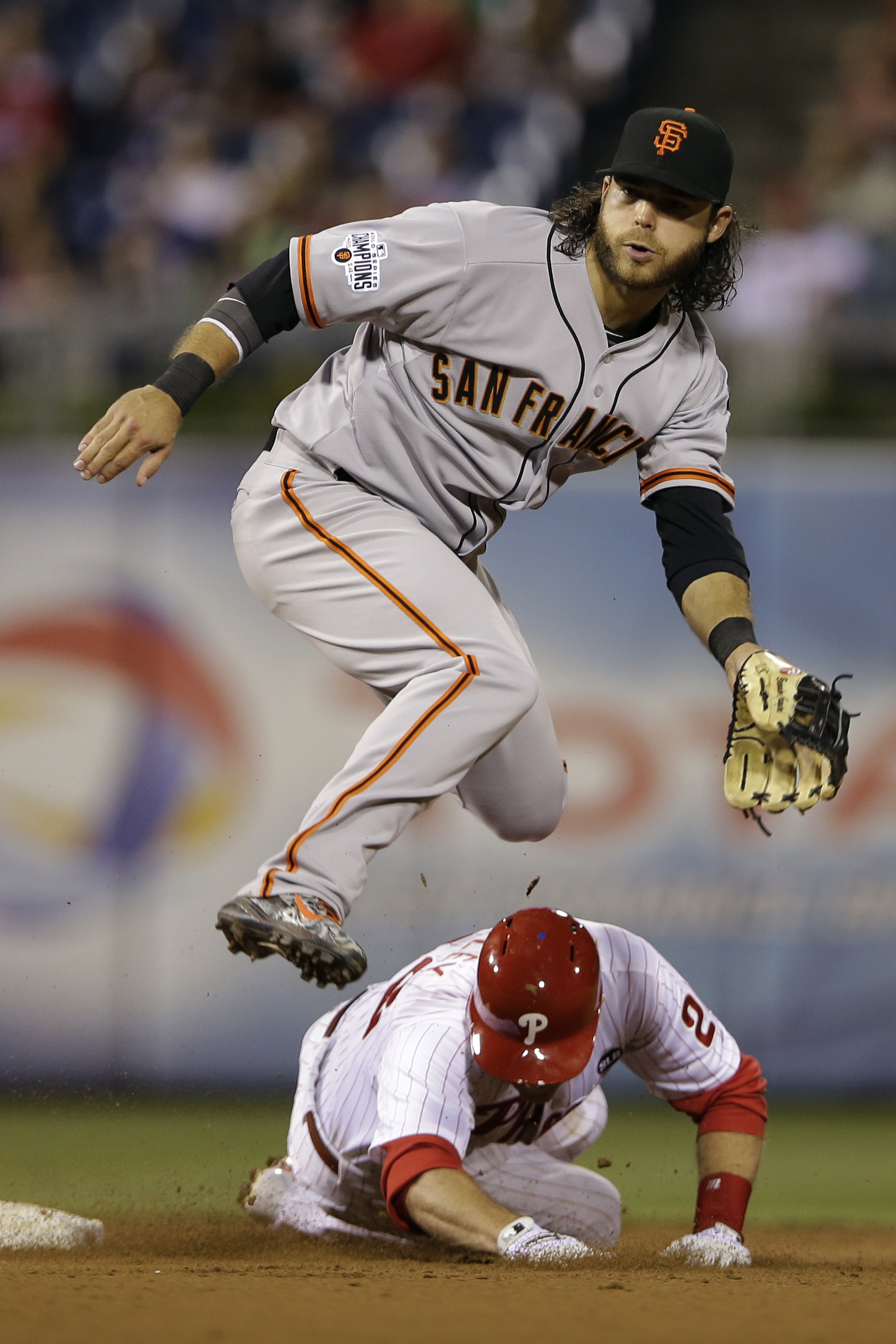 San Francisco Giants shortstop Brandon Crawford, top, leaps over Philadelphia Phillies' Chase Utley after forcing Utley out at second base on a double play hit into by Ryan Howard during the eighth inning of a baseball game, Friday, June 5, 2015, in Phila