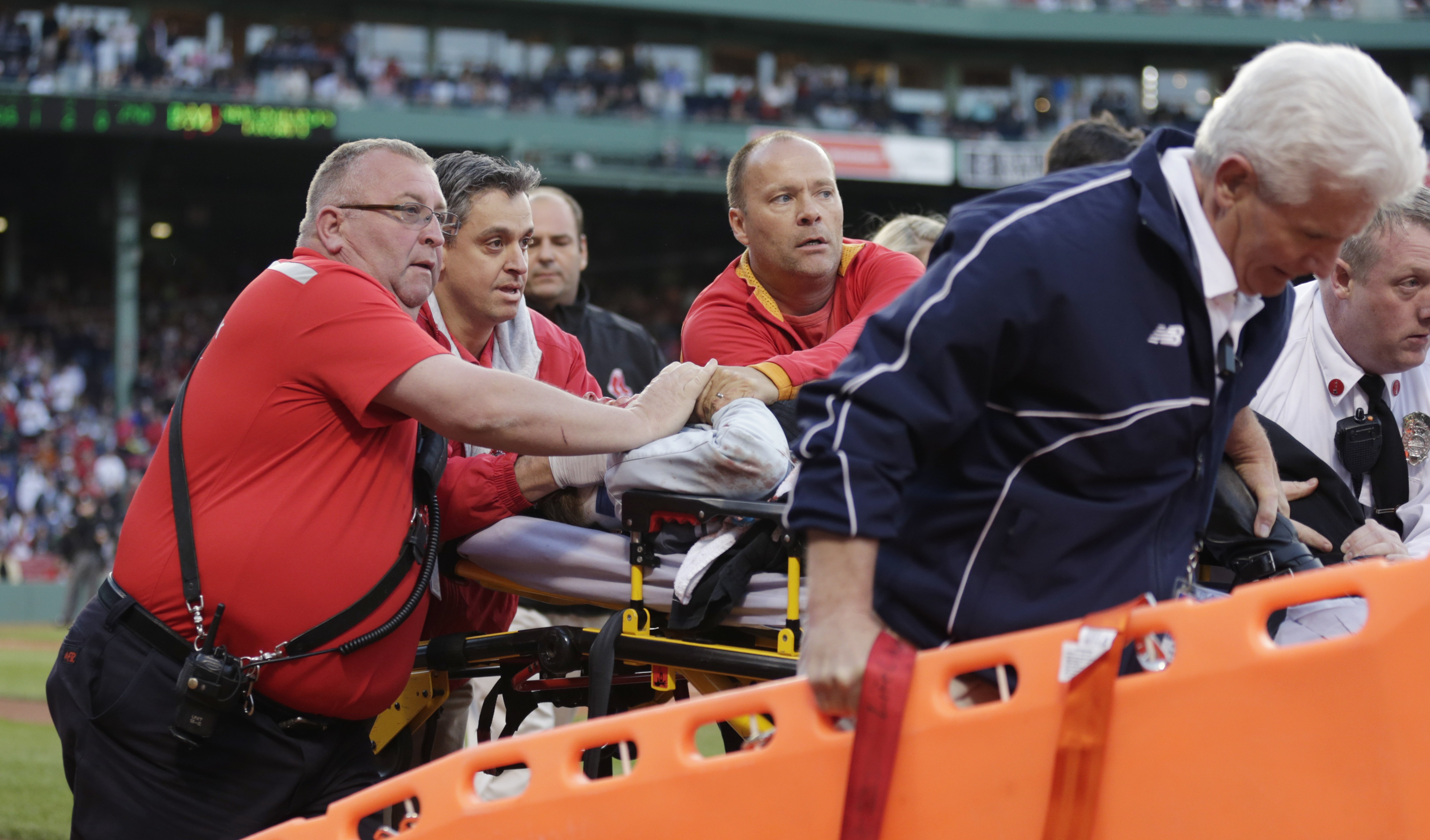Boston Red Sox medical personnel tend to a woman, who with was hit by a wooden shard, off a broken bat of Oakland Athletics' Brett Lawrie, in the second inning during a baseball game at Fenway Park in Boston, Friday, June 5, 2015. The game stopped as the