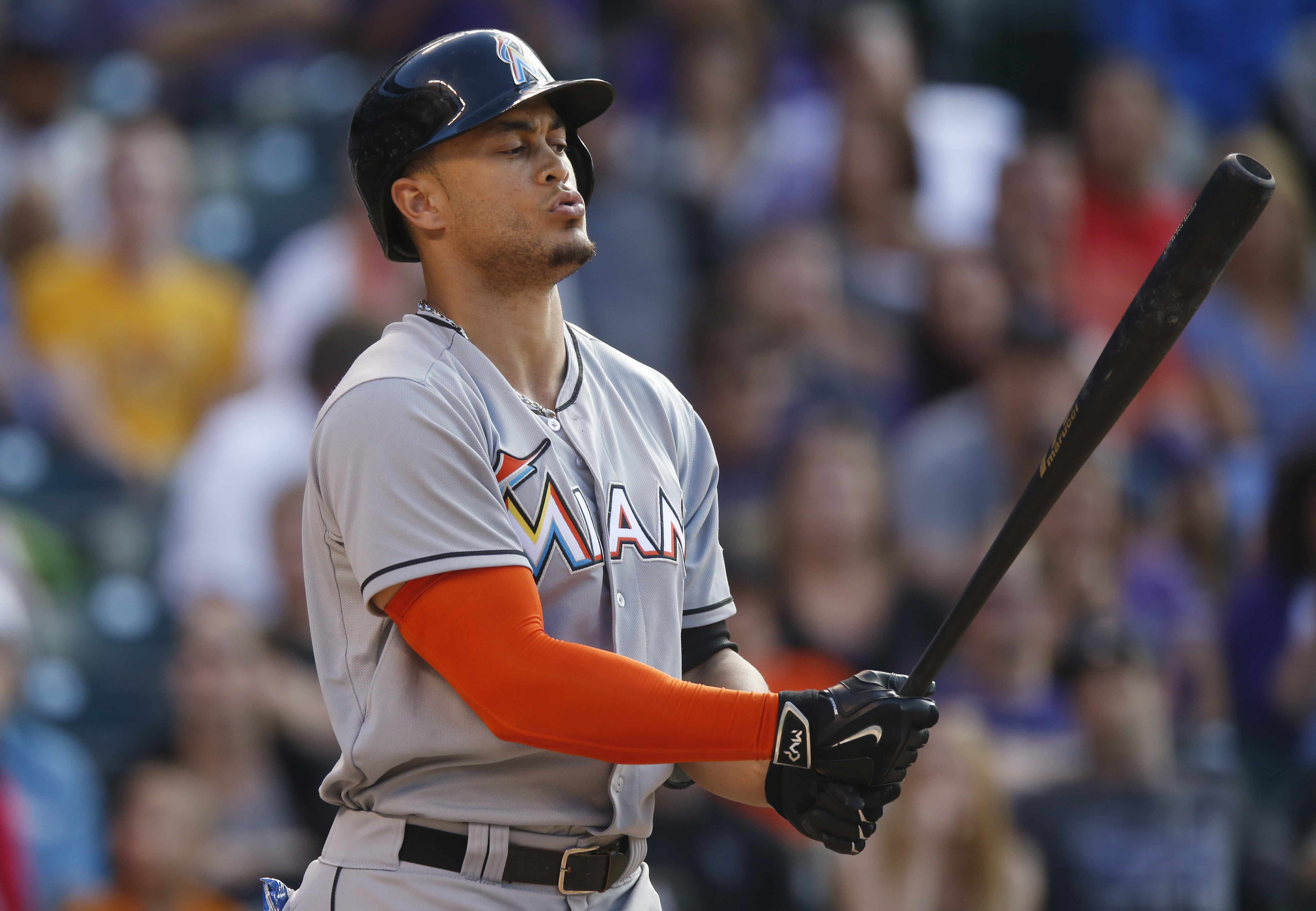 Miami Marlins' Giancarlo Stanton reacts after swinging and missing a pitch from Colorado Rockies starting pitcher Chris Rusin in the seventh inning of a baseball game Saturday, June 6, 2015, in Denver. (AP Photo/David Zalubowski)