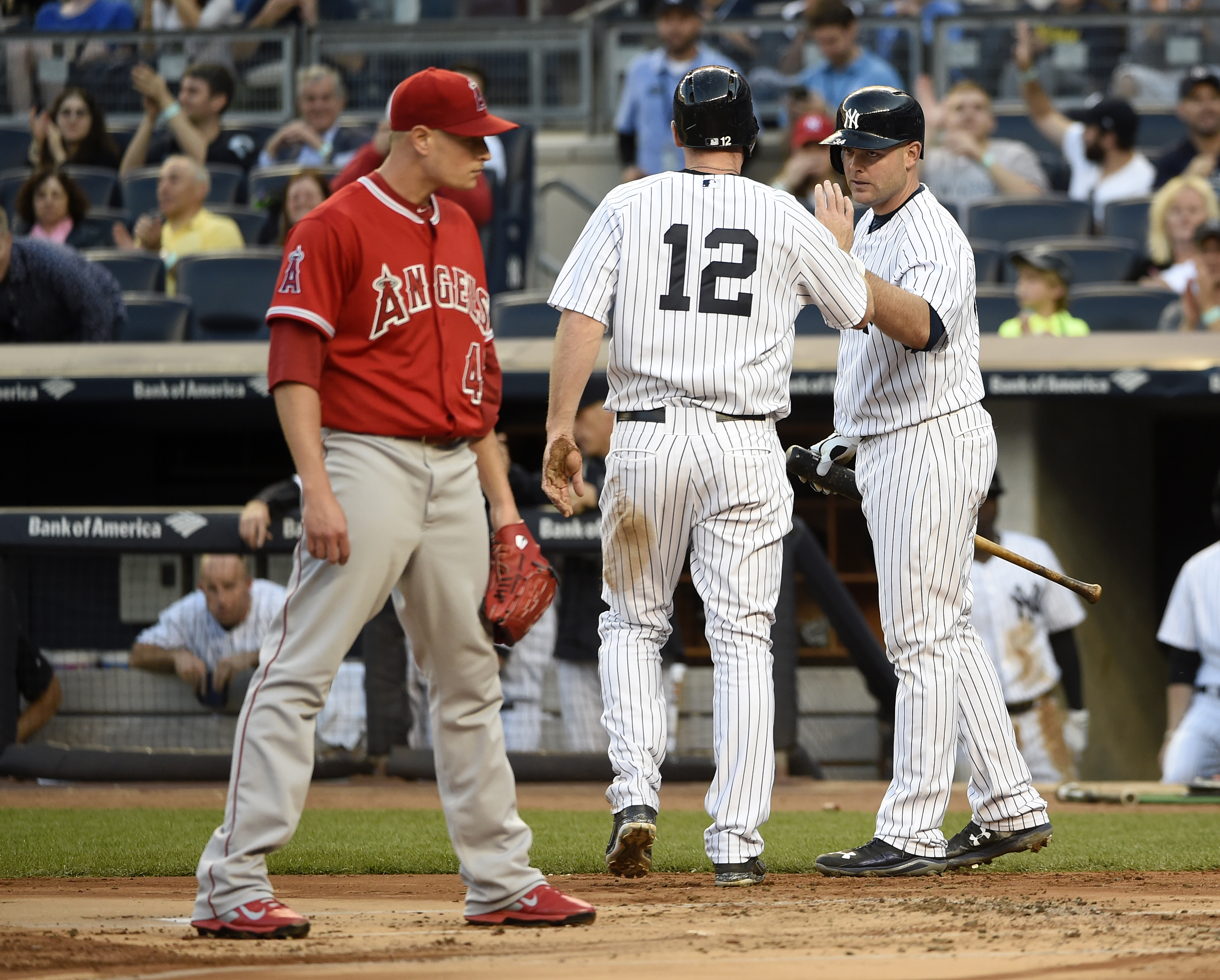 Los Angeles Angels starting pitcher Garrett Richards reacts at home plate as New York Yankees' Chase Headley (12) is greeted by Brian McCann after Headley scored on a wild pitch in the first inning of a baseball game at Yankee Stadium on Saturday, June 6,