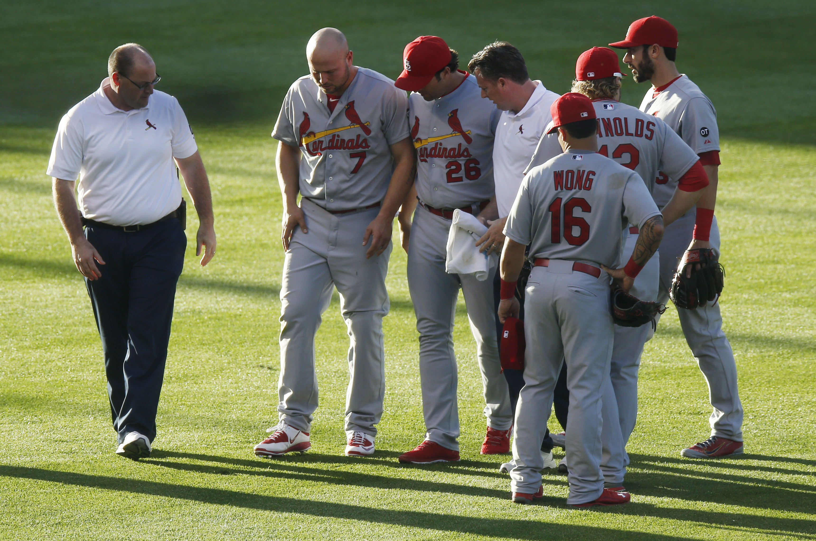 St. Louis Cardinals left fielder Matt Holliday, second from left, is helped off the field by St. Louis Cardinals manager Mike Matheny as trainers and teammates look on after Holliday was injured while pursuing a fly ball in the second inning of a baseball