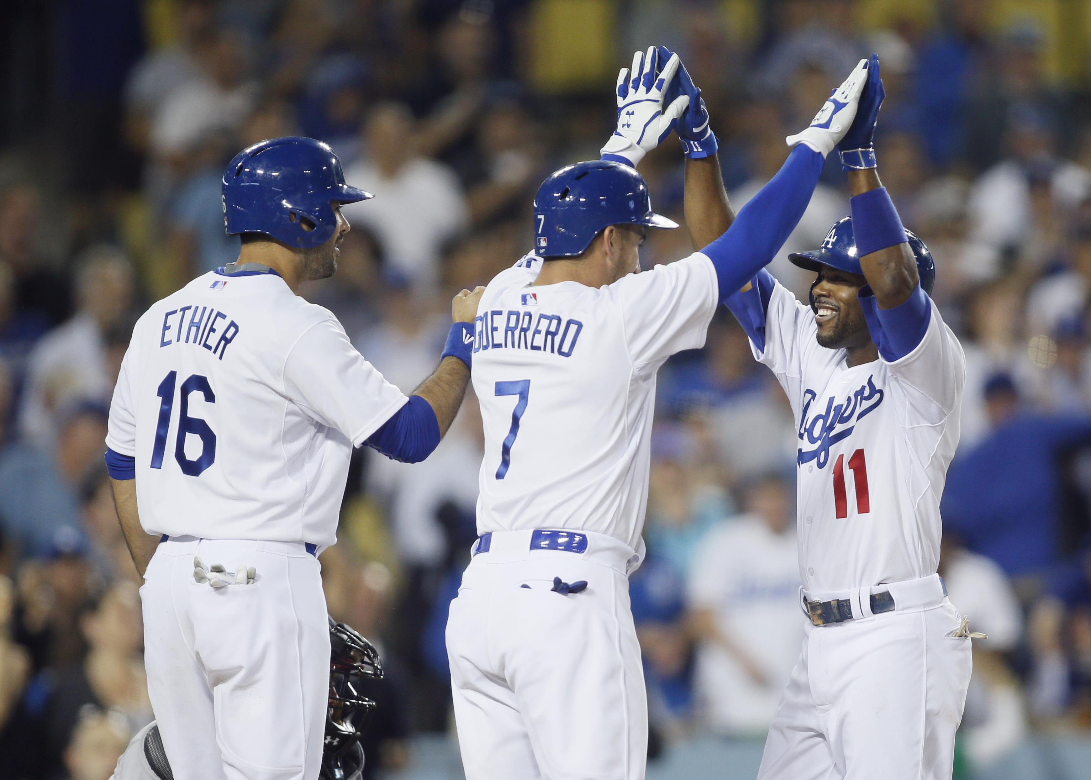 Los Angeles Dodgers shortstop Jimmy Rollins, right, celebrates his three-run home run after driving in Alex Guerrero, center, and Andre Ethier, left, during the fourth inning of a baseball game against the Arizona Diamondbacks, Monday, June 8, 2015, in Lo