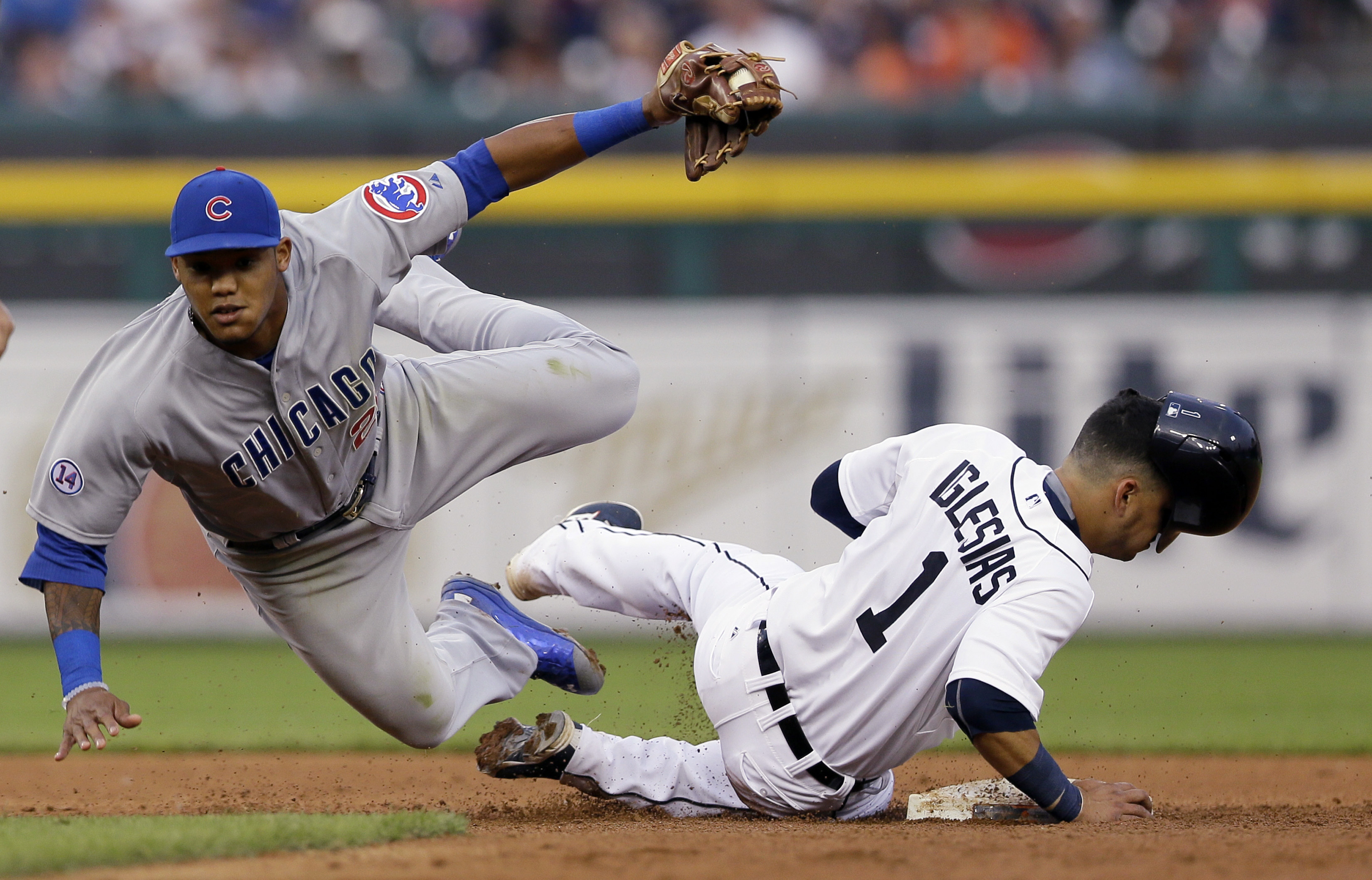 Chicago Cubs second baseman Addison Russell tumbles next to Detroit Tigers' Jose Iglesias after tagging Iglesias out on an attempted steal during the fifth inning of a baseball game, Tuesday, June 9, 2015, in Detroit. (AP Photo/Carlos Osorio)