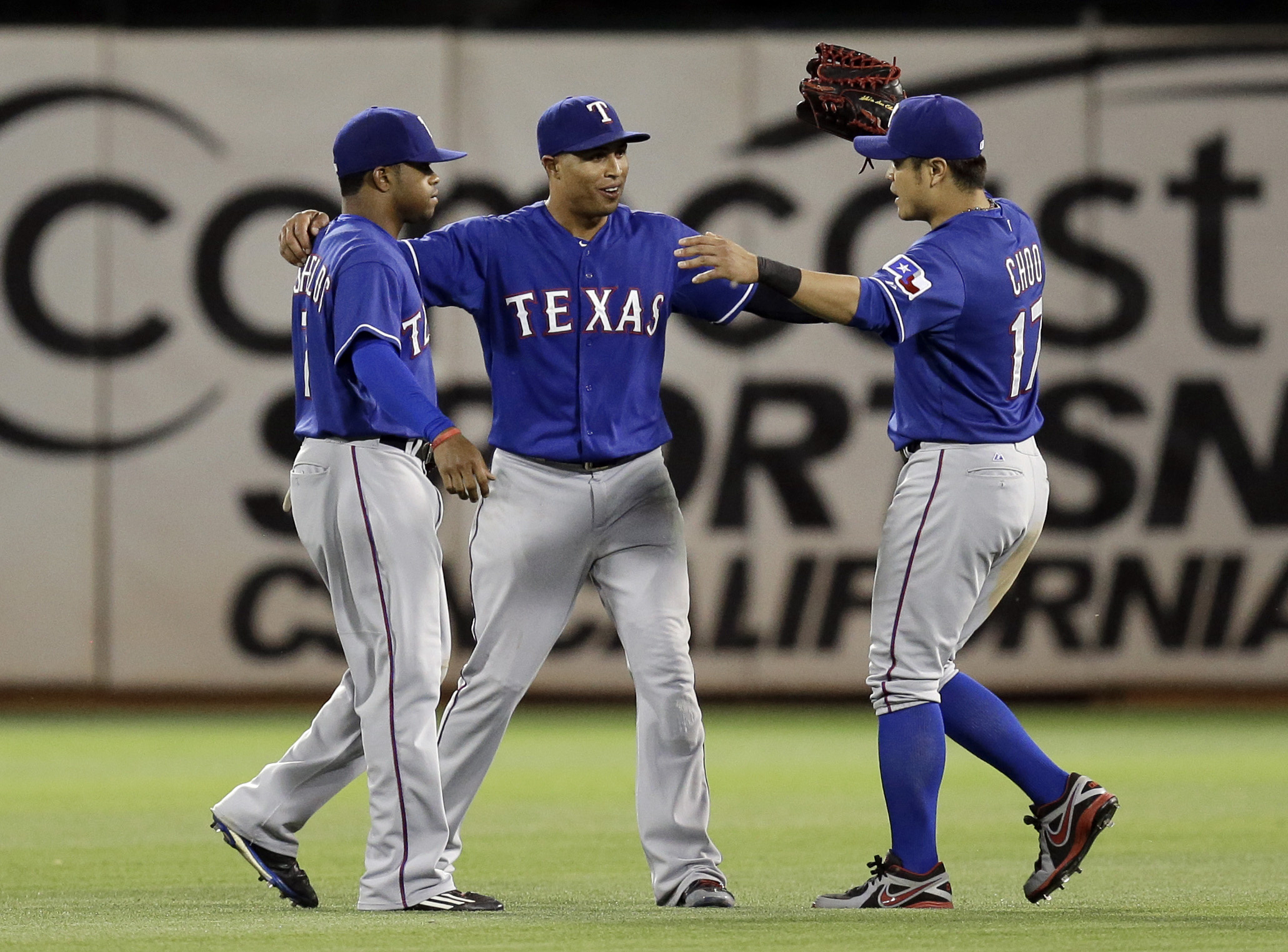 From left, Texas Rangers' Delino DeShields, Leonys Martin and Shin-Soo Choo celebrate defeating the Oakland Athletics 2-1 at the end of a baseball game Tuesday, June 9, 2015, in Oakland, Calif. (AP Photo/Ben Margot)