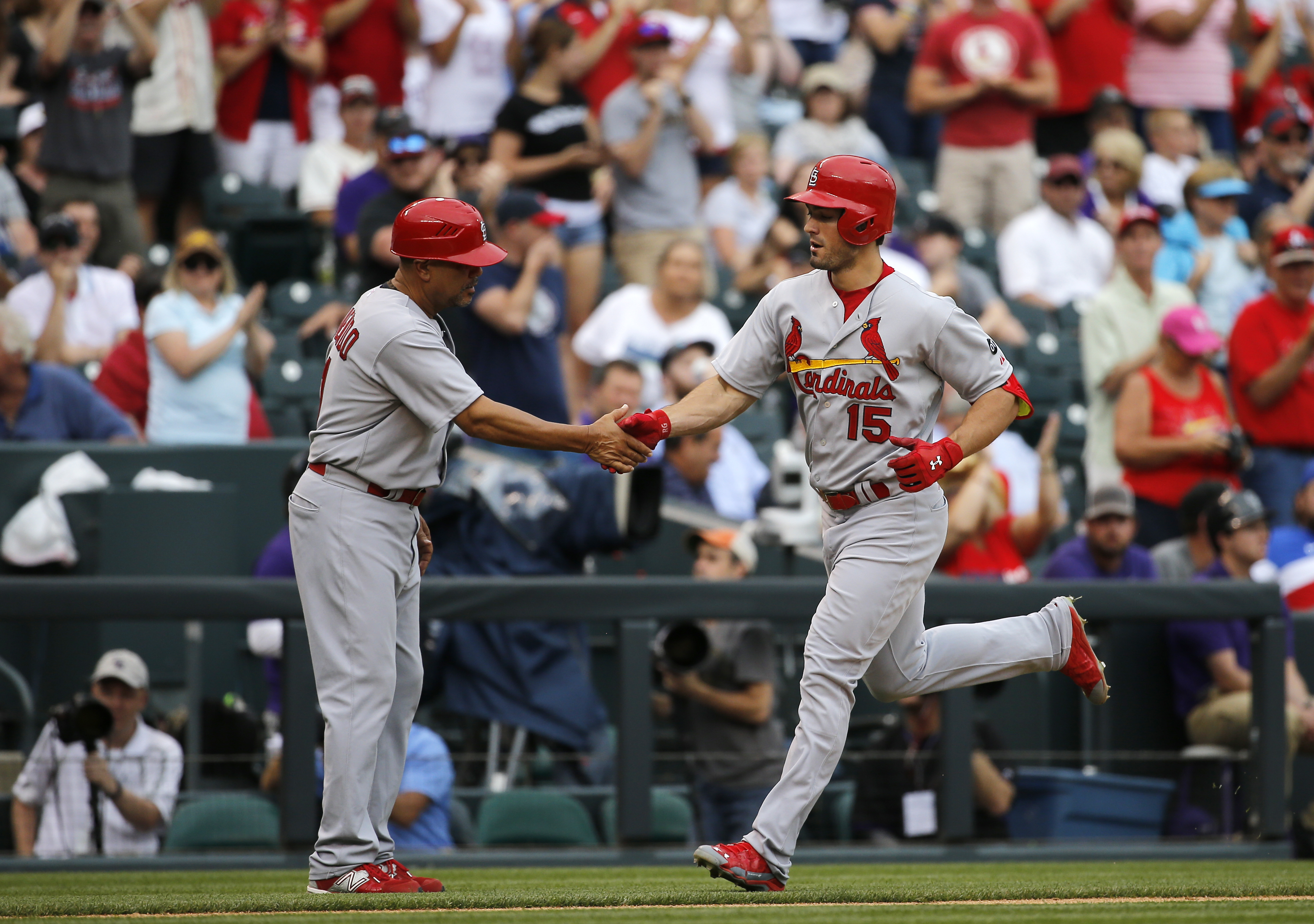 St. Louis Cardinals' Randal Grichuk (15) is congratulated by Jose Oquendo (11) after hitting a solo home run against the Colorado Rockies during the eighth inning of a baseball game, Wednesday, June 10, 2015, in Denver. (AP Photo/Jack Dempsey)