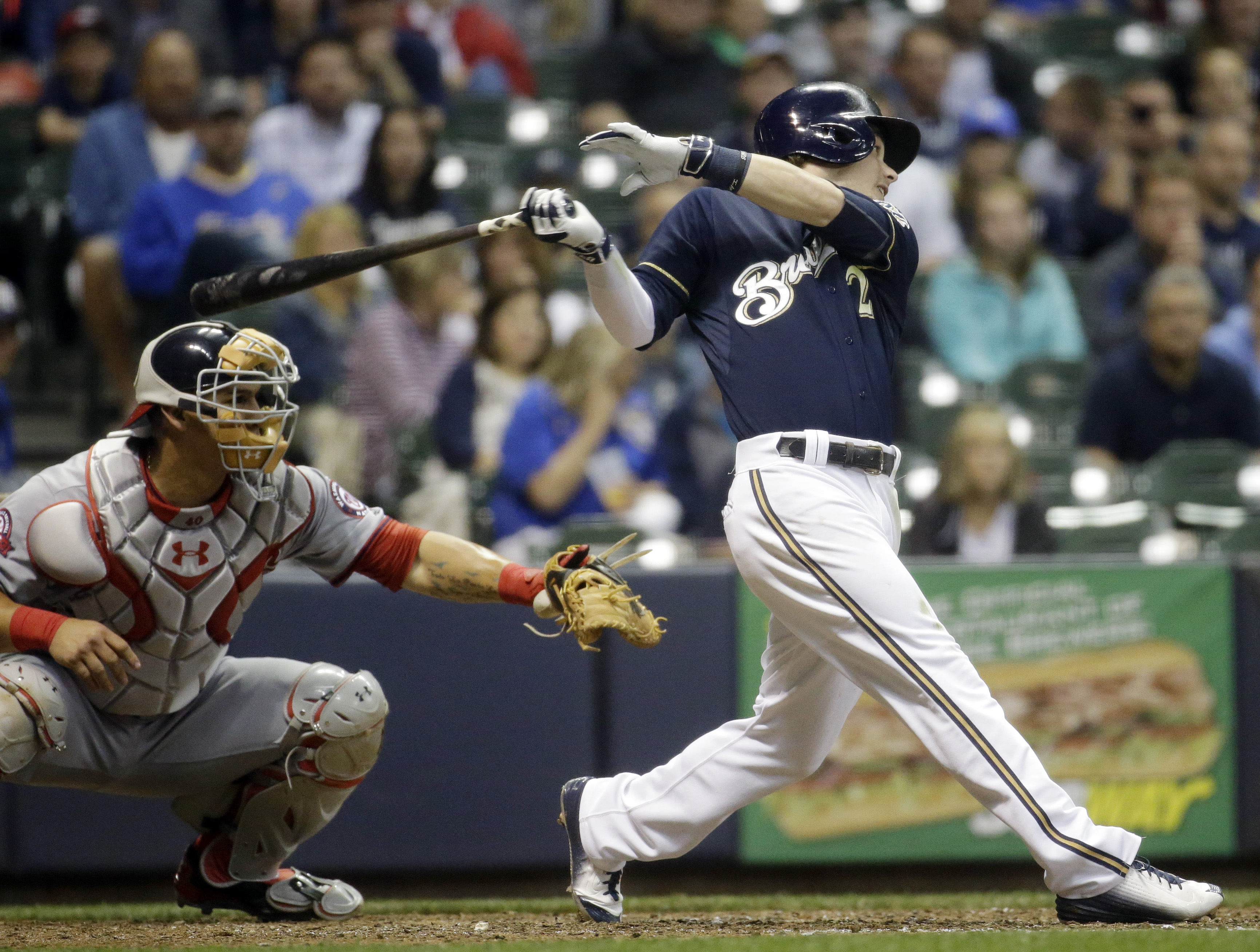 Milwaukee Brewers' Scooter Gennett, right, hits an RBI-single during the eighth inning of a baseball game against the Washington Nationals, Thursday, June 11, 2015, in Milwaukee. (AP Photo/Morry Gash)
