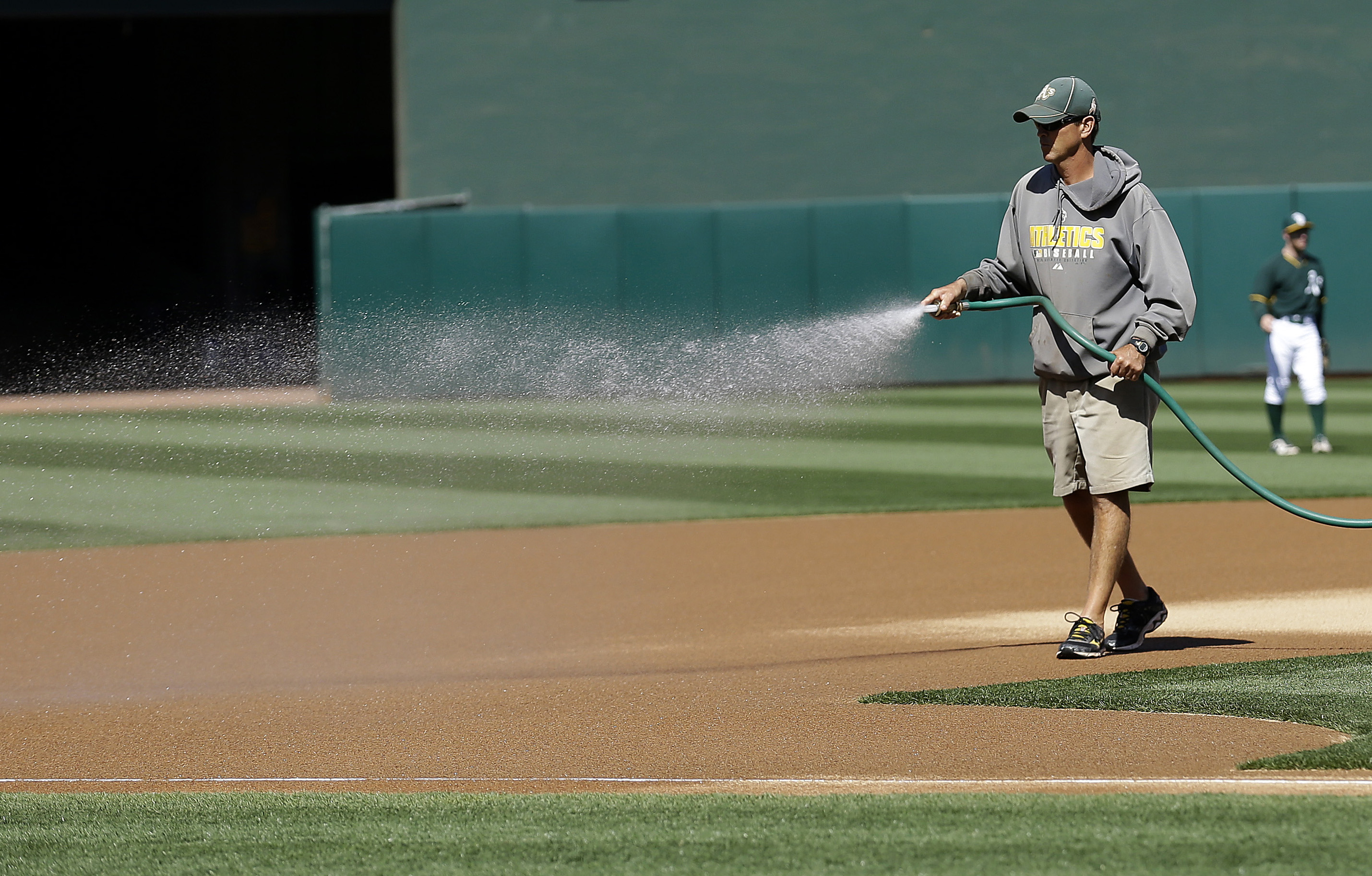 In this photo taken May 26, 2015, Oakland Athletics head groundskeeper Clay Wood waters down the infield at O.co Coliseum before a baseball game between the Athletics and the Detroit Tigers in Oakland, Calif. California's severe drought is affecting how b