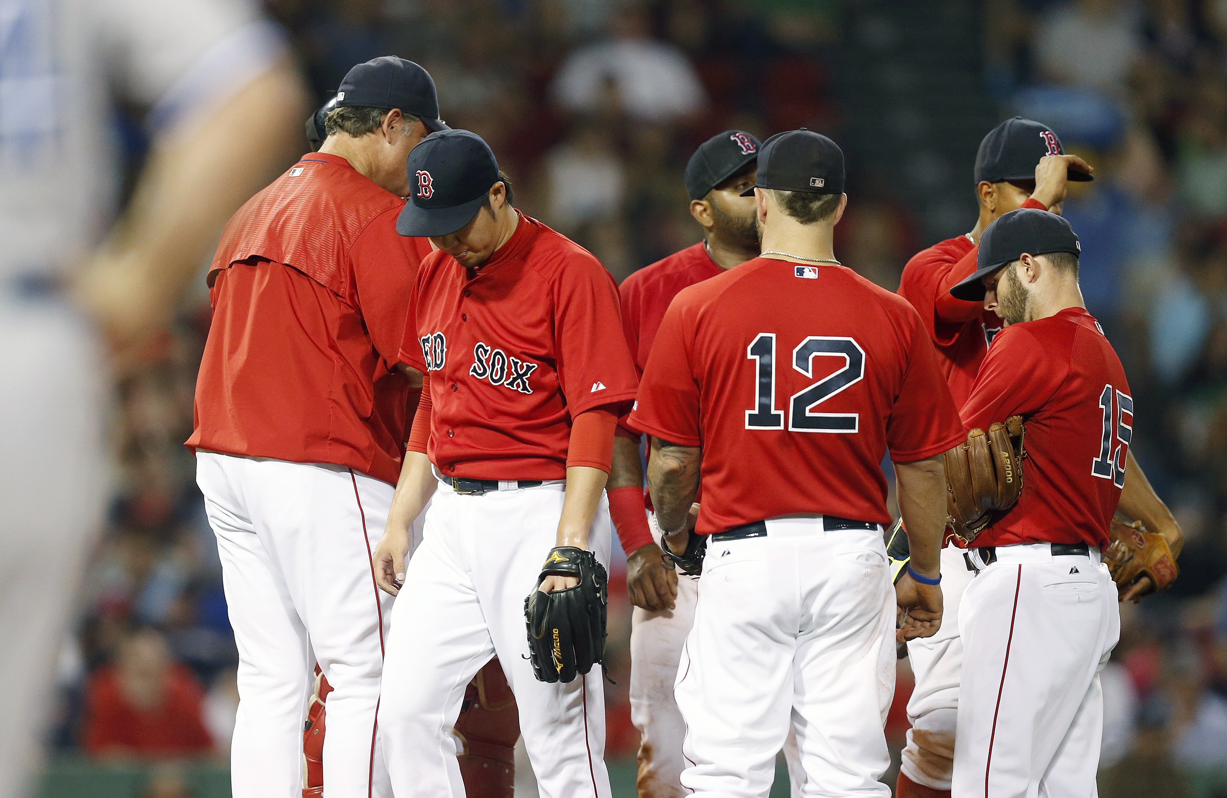 Boston Red Sox's Junichi Tazawa, second from left, walks past manager John Farrell, left, after being taken out during the seventh inning of a baseball game against the Toronto Blue Jays in Boston, Friday, June 12, 2015. (AP Photo/Michael Dwyer)