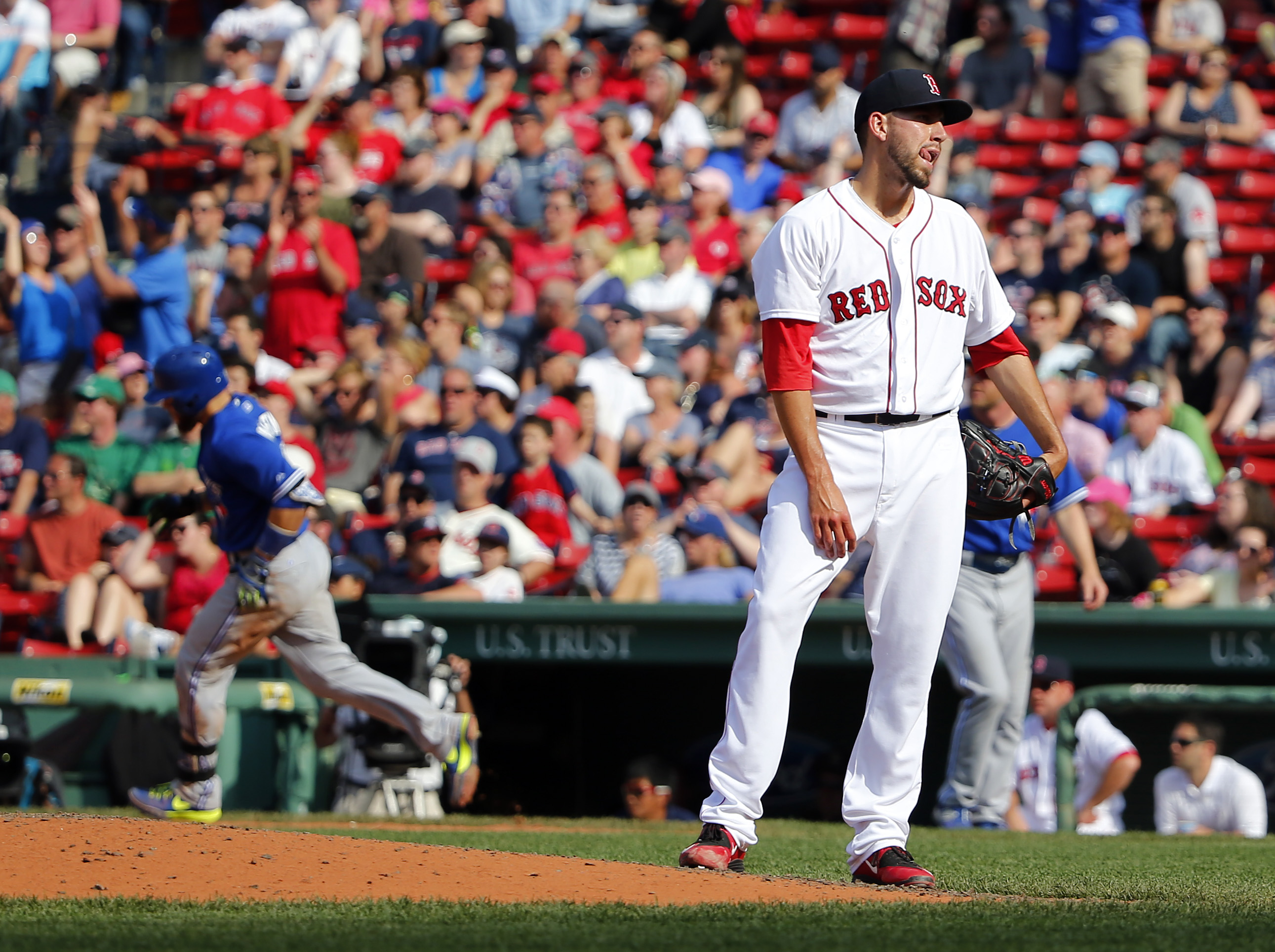 Boston Red Sox relief pitcher Matt Barnes stands on the mound after giving up the winning home run to Toronto Blue Jays' Russell Martin, left, during the 11th inning of Toronto's 5-4 win in a baseball game at Fenway Park in Boston Saturday, June 13, 2015.