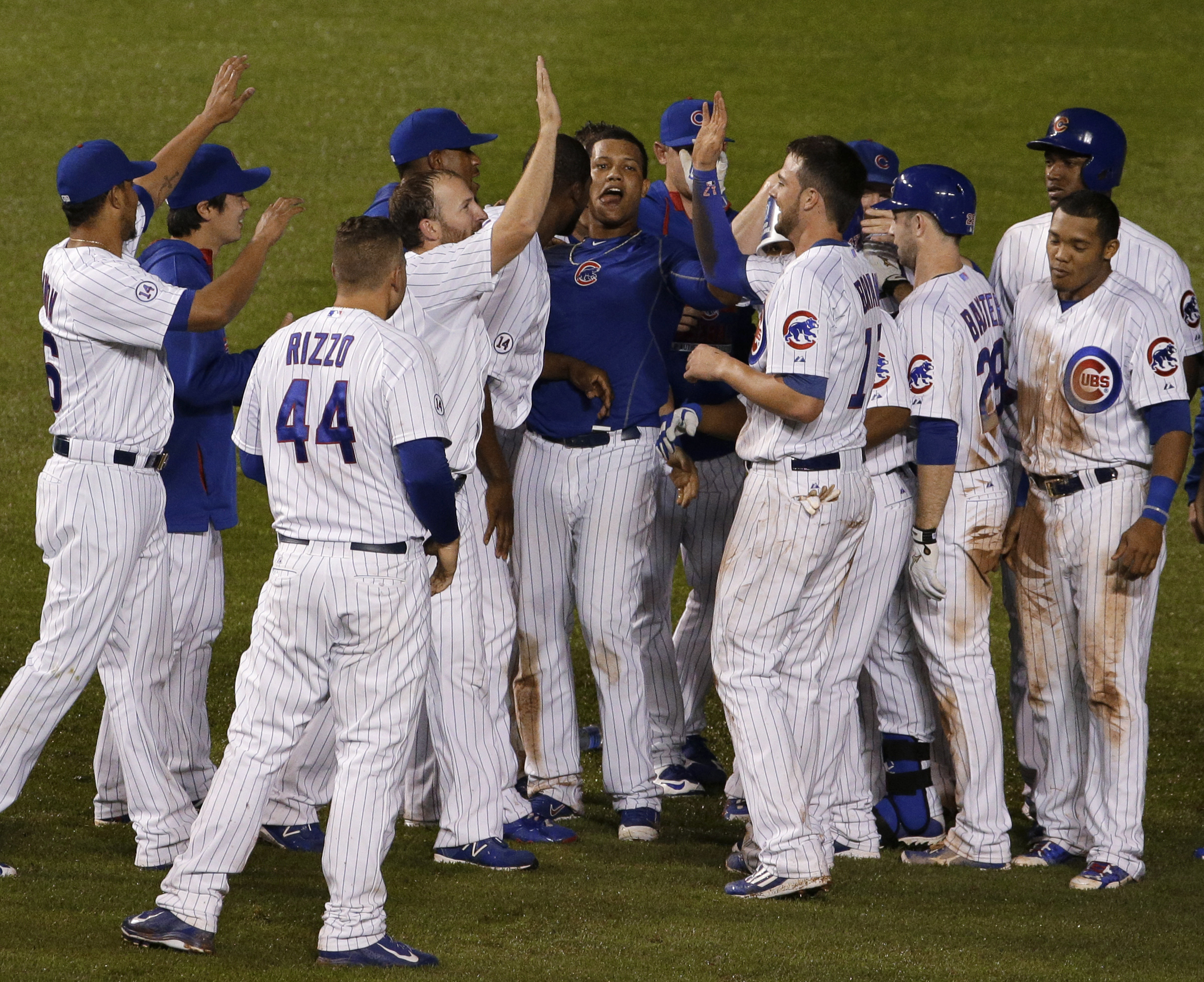 Chicago Cubs' Starlin Castro, center, celebrate with teammates after hitting the game-winning single during the ninth inning of a baseball game against the Cincinnati Reds on Saturday, June 13, 2015, in Chicago. The Cubs won 4-3. (AP Photo/Nam Y. Huh)
