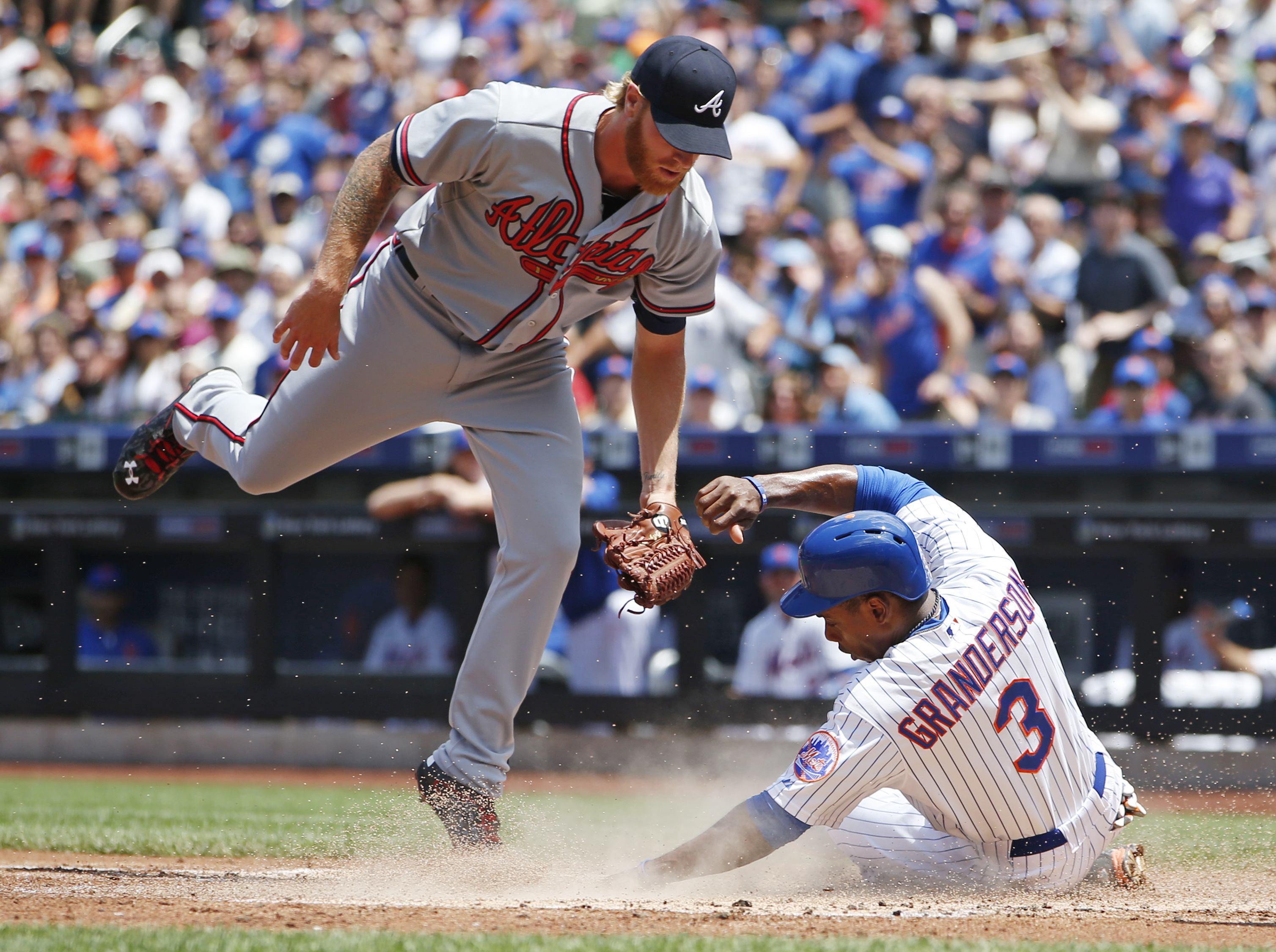 Atlanta Braves starting pitcher Mike Foltynewicz, left, has no play as New York Mets Curtis Granderson (3) slides in to score on a passed ball in the first inning of a baseball game in New York, Sunday, June 14, 2015. (AP Photo/Kathy Willens)