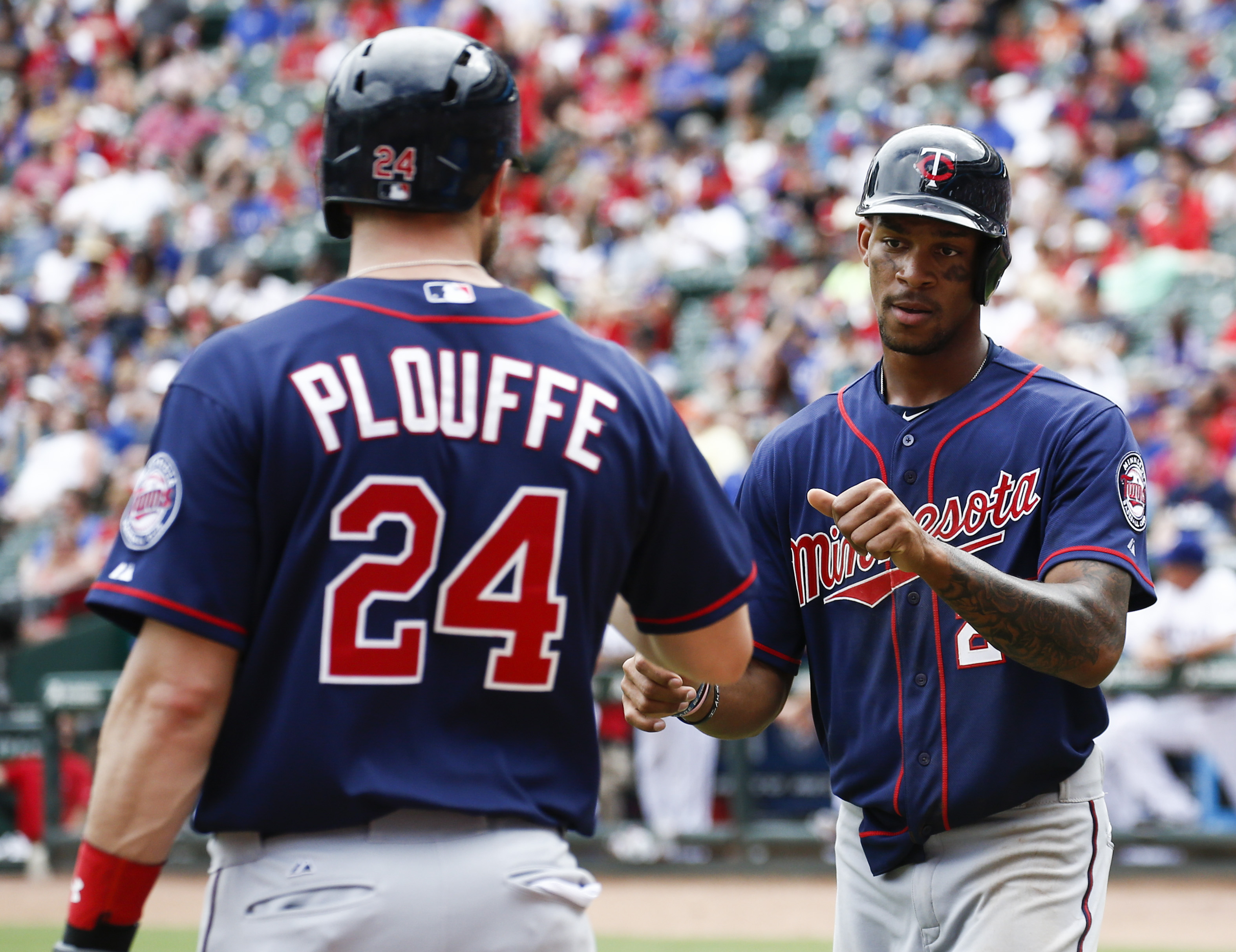 Minnesota Twins' Byron Buxton, right, is congratulated by Trevor Plouffe (24) after scoring the go-ahead run on a double by Eddie Rosario against the Texas Rangers during the ninth inning of a baseball game, Sunday, June 14, 2015, in Arlington, Texas. The