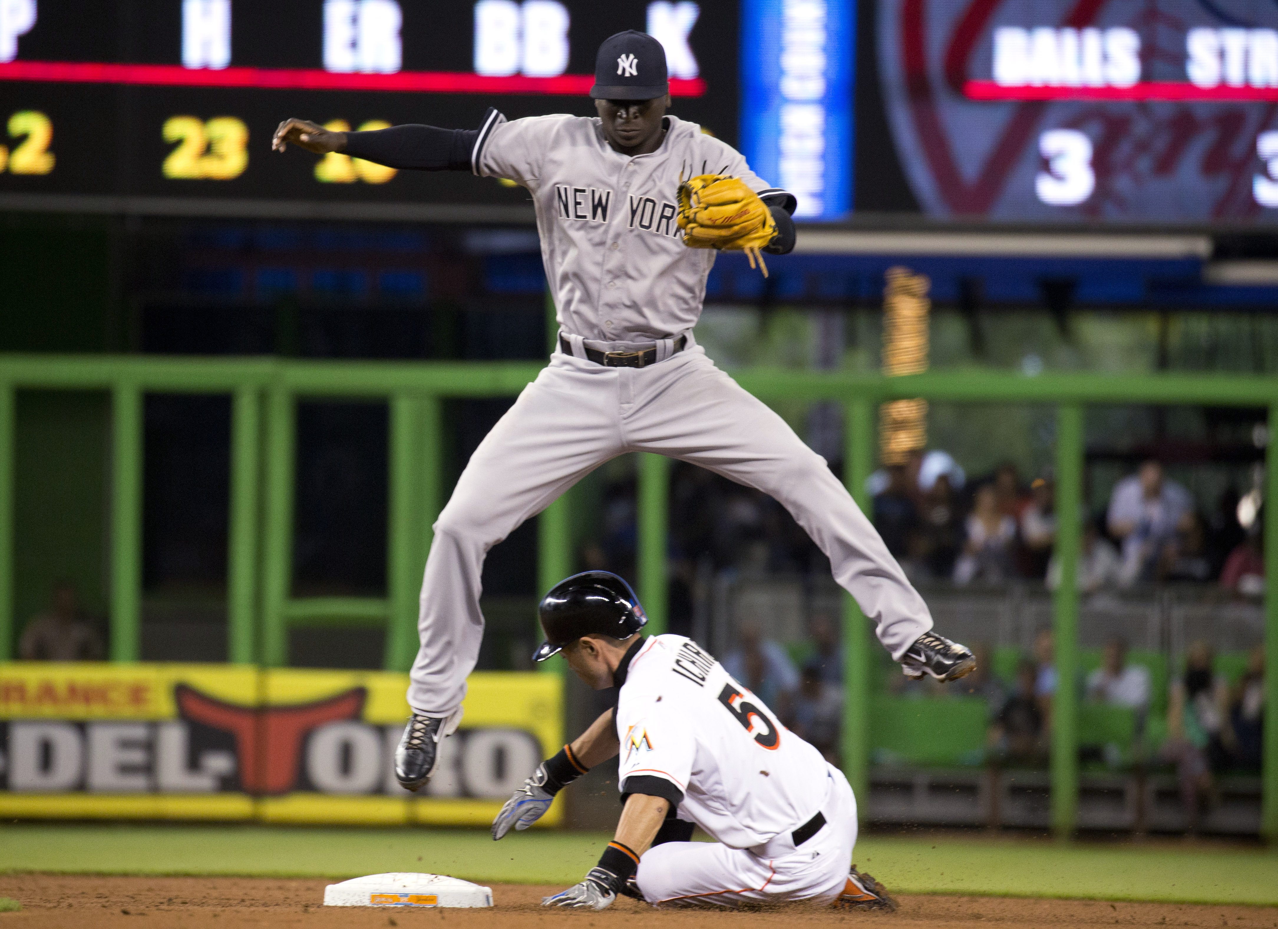 New York Yankees shortstop Didi Gregorius hops over Miami Marlins' Ichiro Suzuki (51) after forcing him out at second during the first inning of a baseball game in Miami, Monday, June 15, 2015. (AP Photo/J Pat Carter)